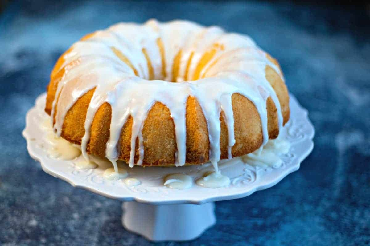 Lemon Bundt Cake with lemon glaze on a white cake stand