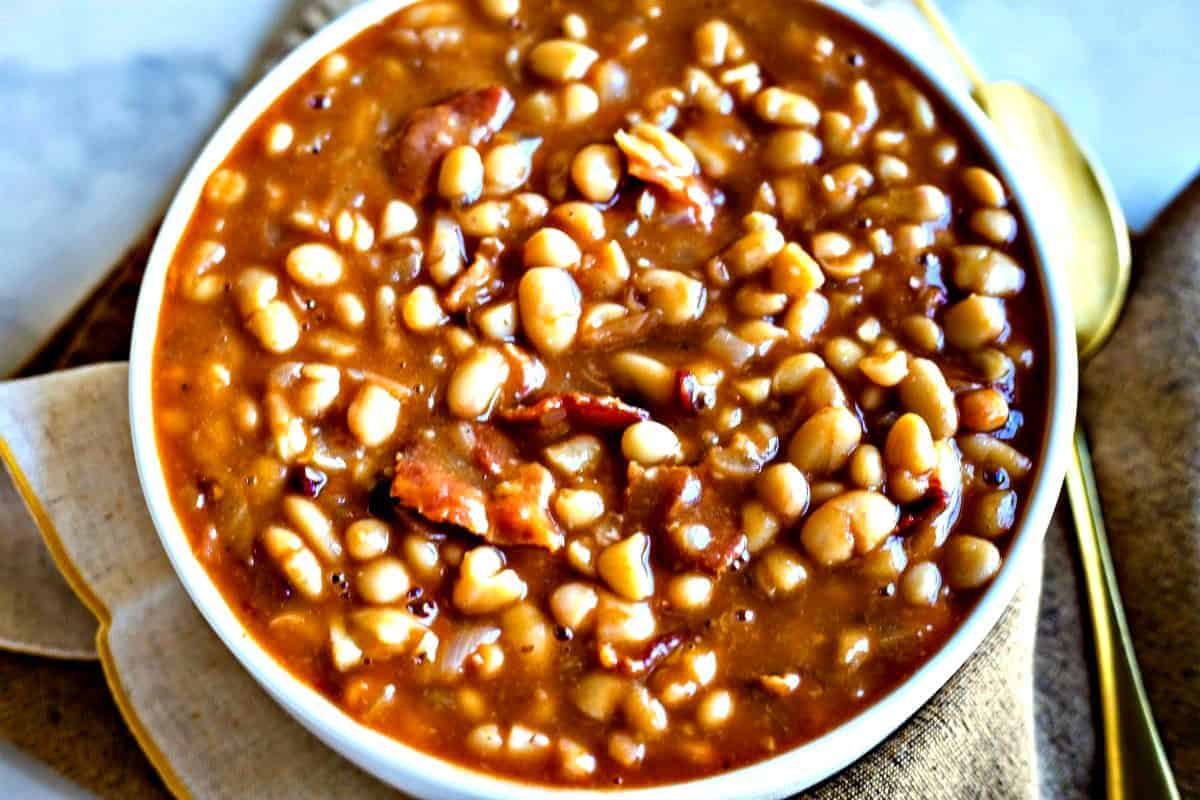 Smoky Chipotle Baked Beans in a white bowl with gold spoon