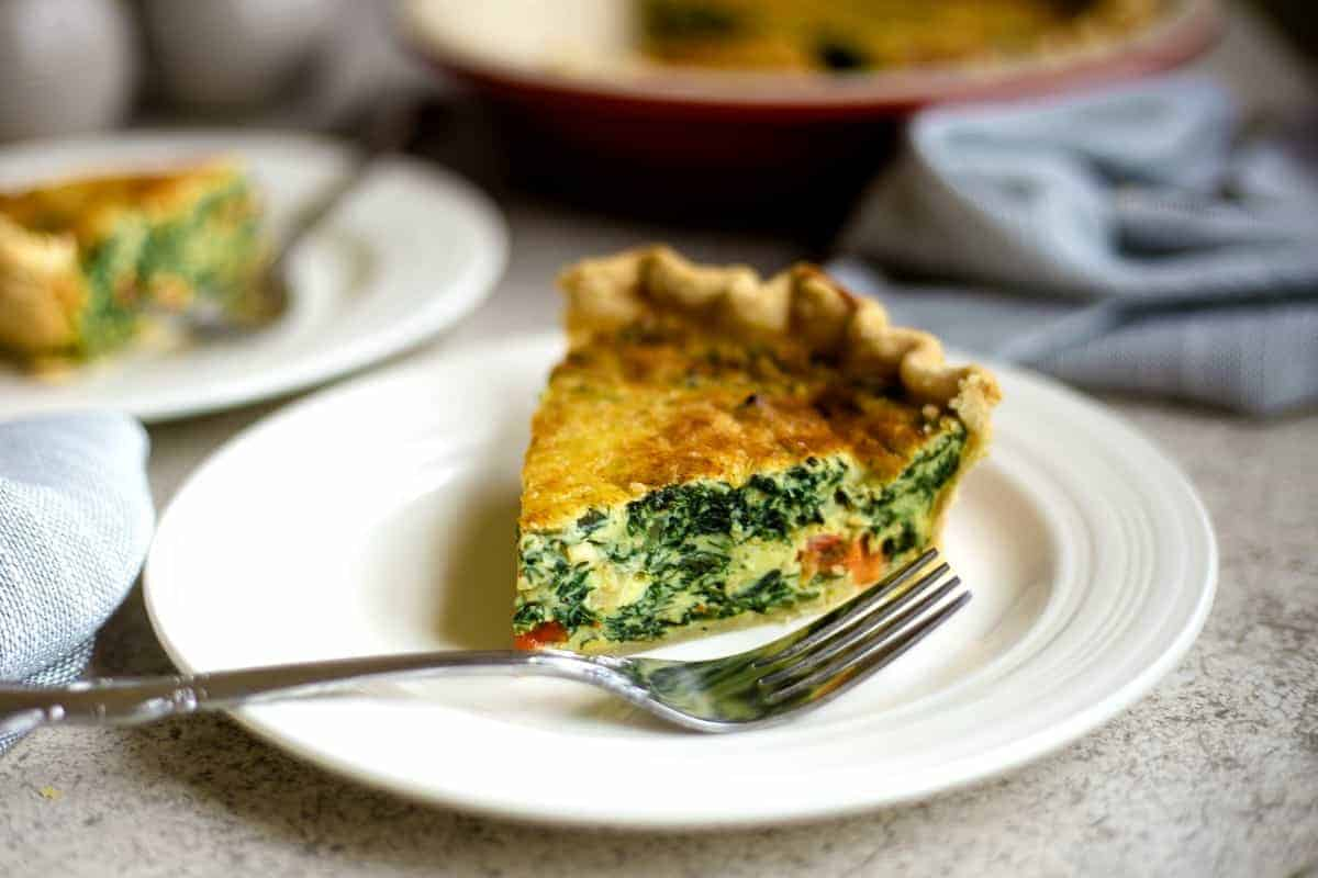 slice of spinach quiche on a white plate