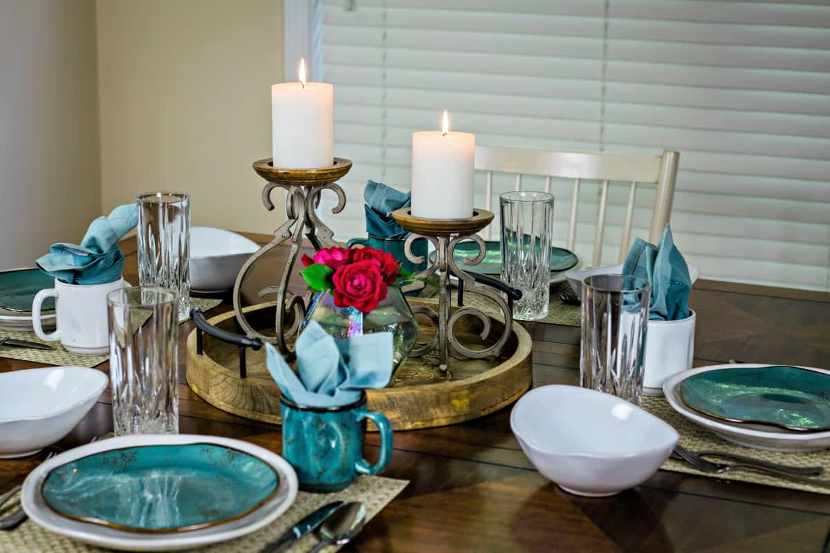table set for a dinner party with candles and roses