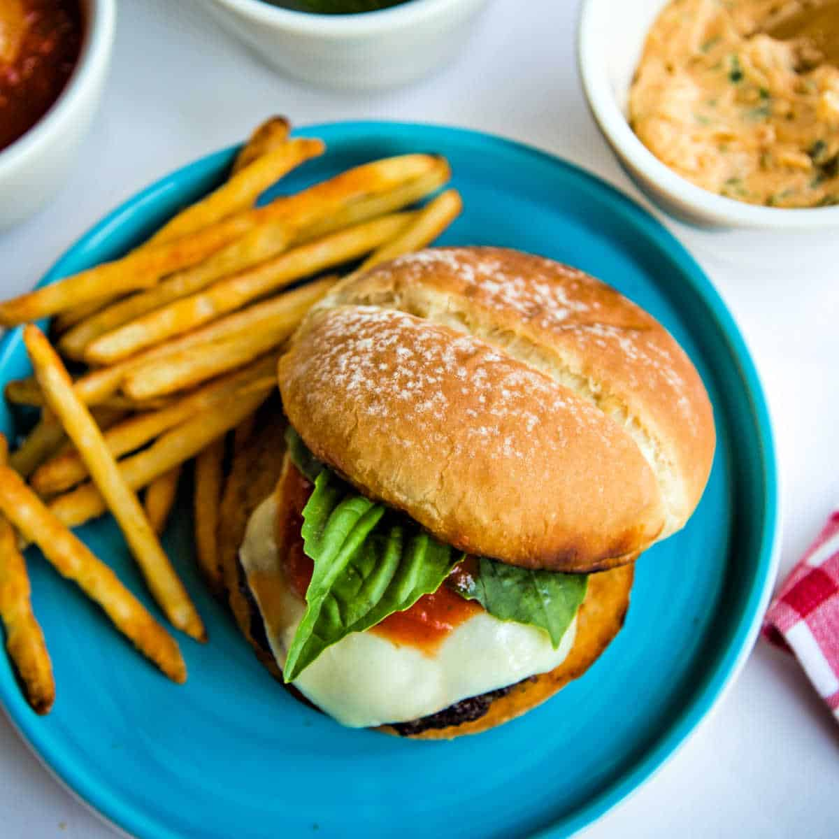 Italian Burgers with Fresh Basil & Roasted Garlic Butter on a blue plate with french fries