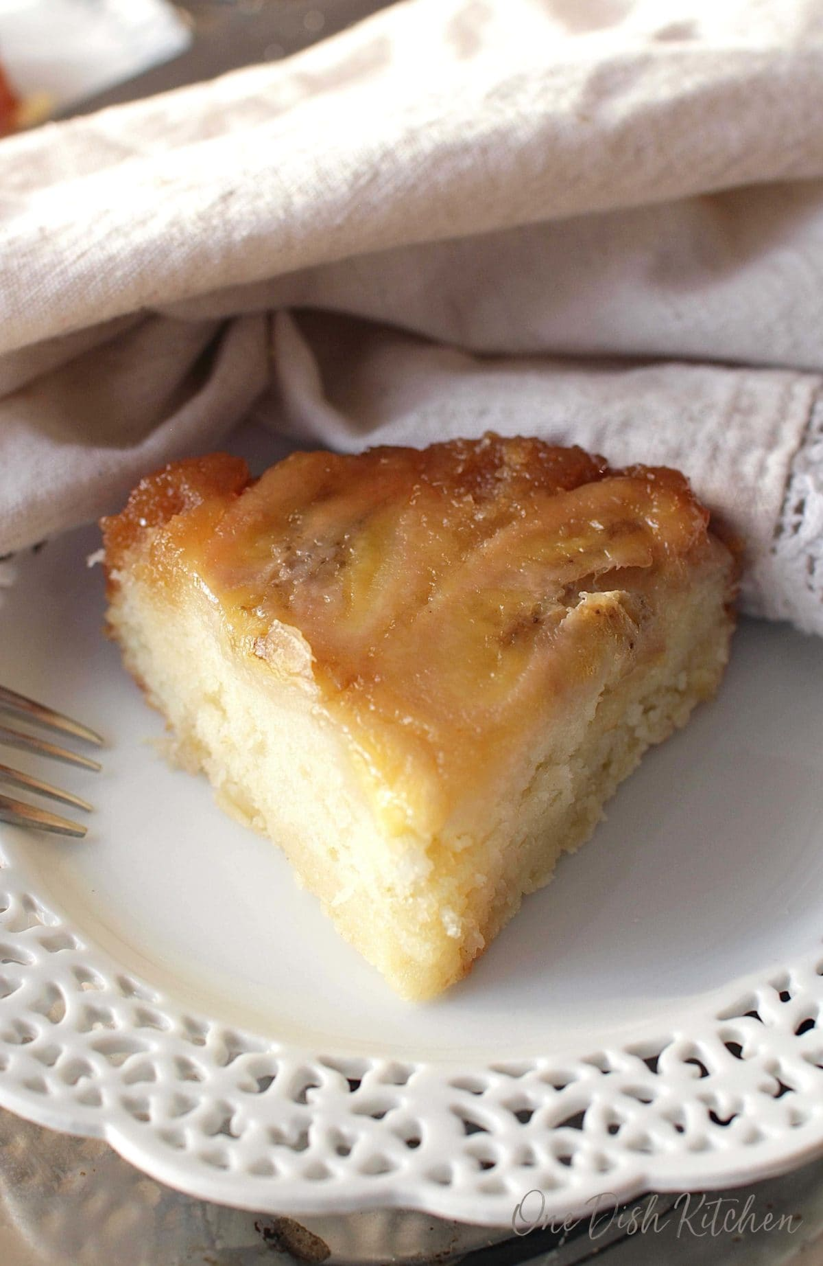 a slice of banana upside down cake on a white lace plate.