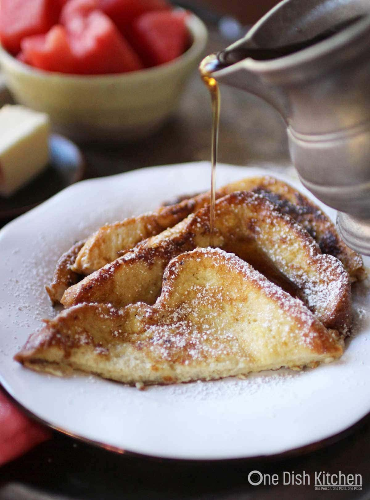 A plate of three slices of french toast dusted with powdered sugar being drizzled with maple syrup