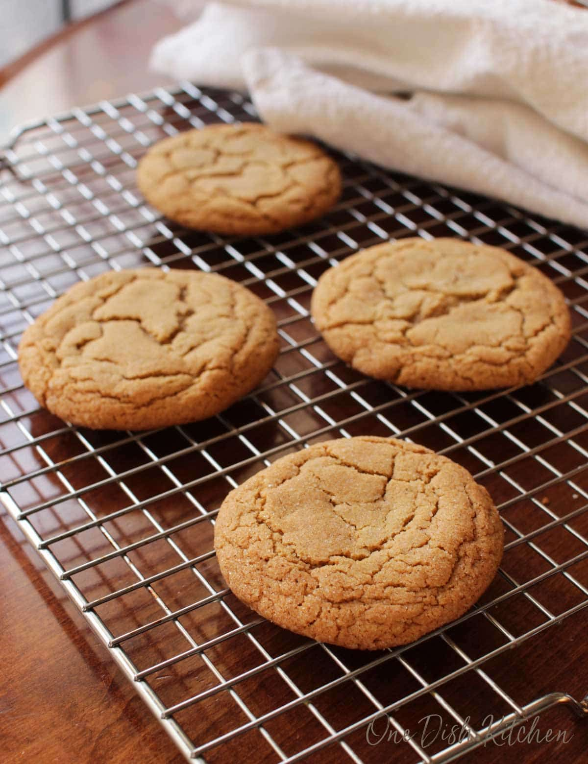 Four soft ginger cookies on a cooling rack