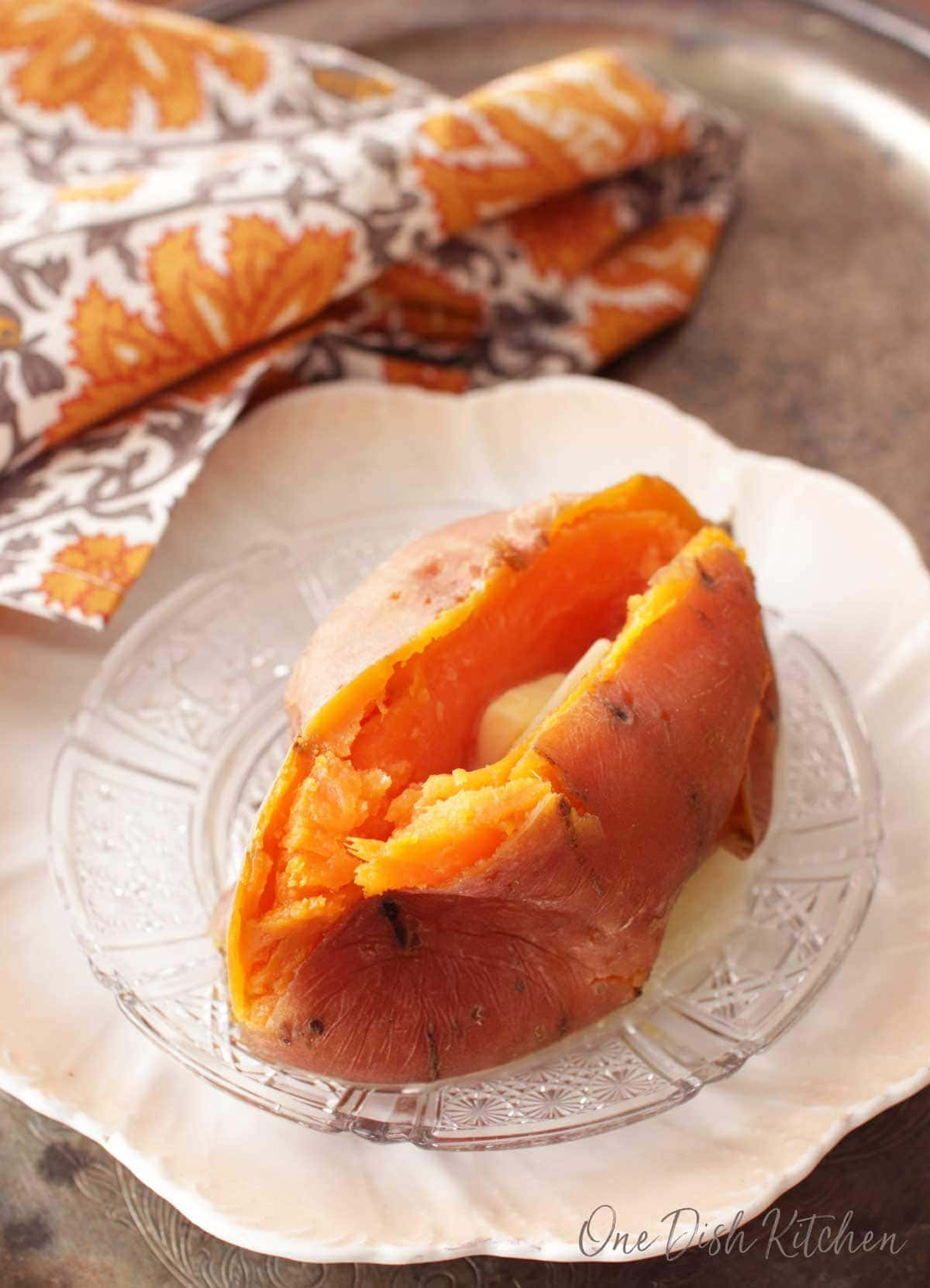 Cooked sweet potato plated on a metal tray with a grey and orange cloth napkin