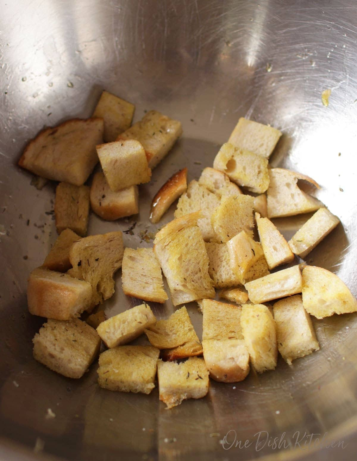 Croutons in a bowl topped with olive oil, salt, and herbs