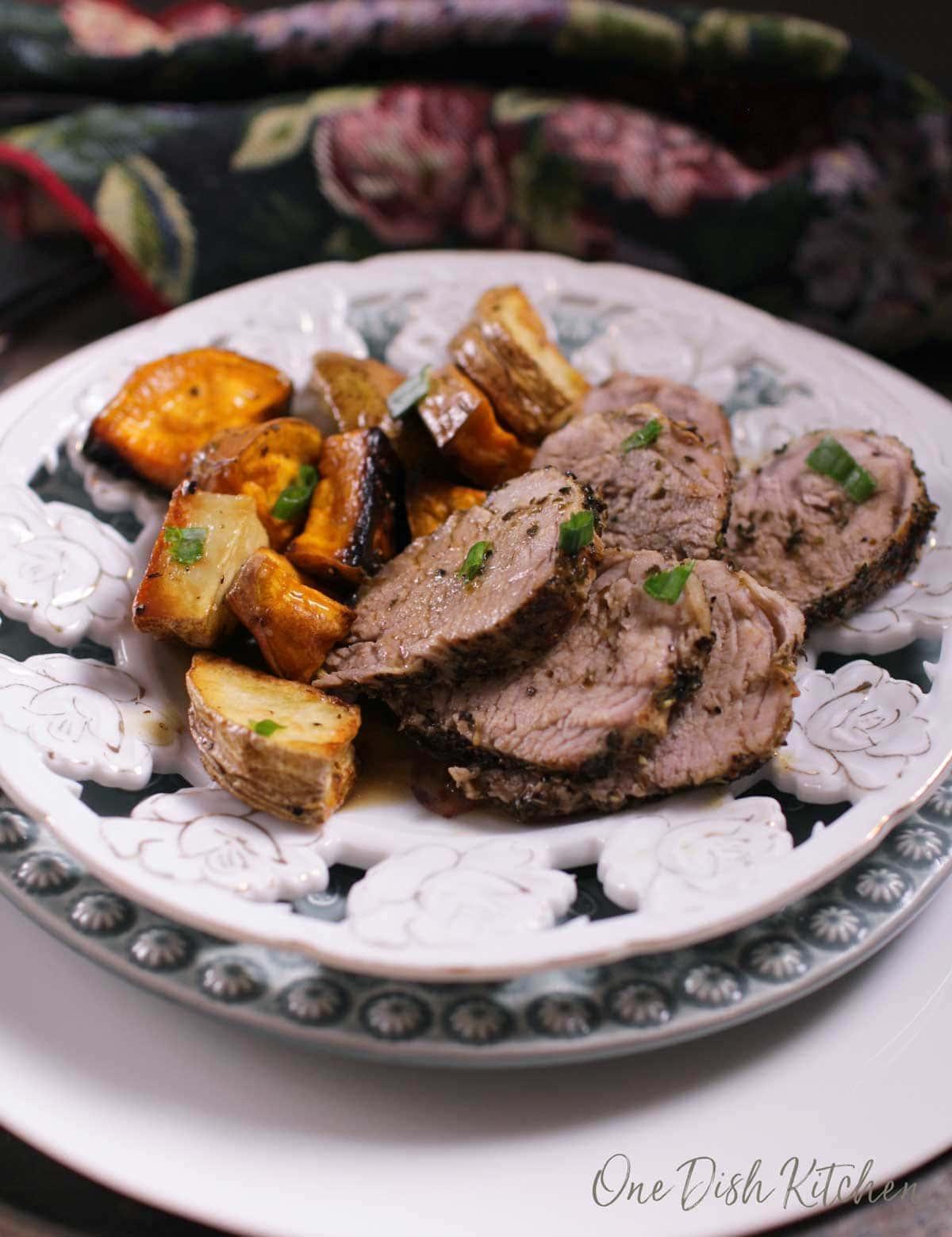 Sliced pork tenderloin and sliced roasted potatoes on a plate.