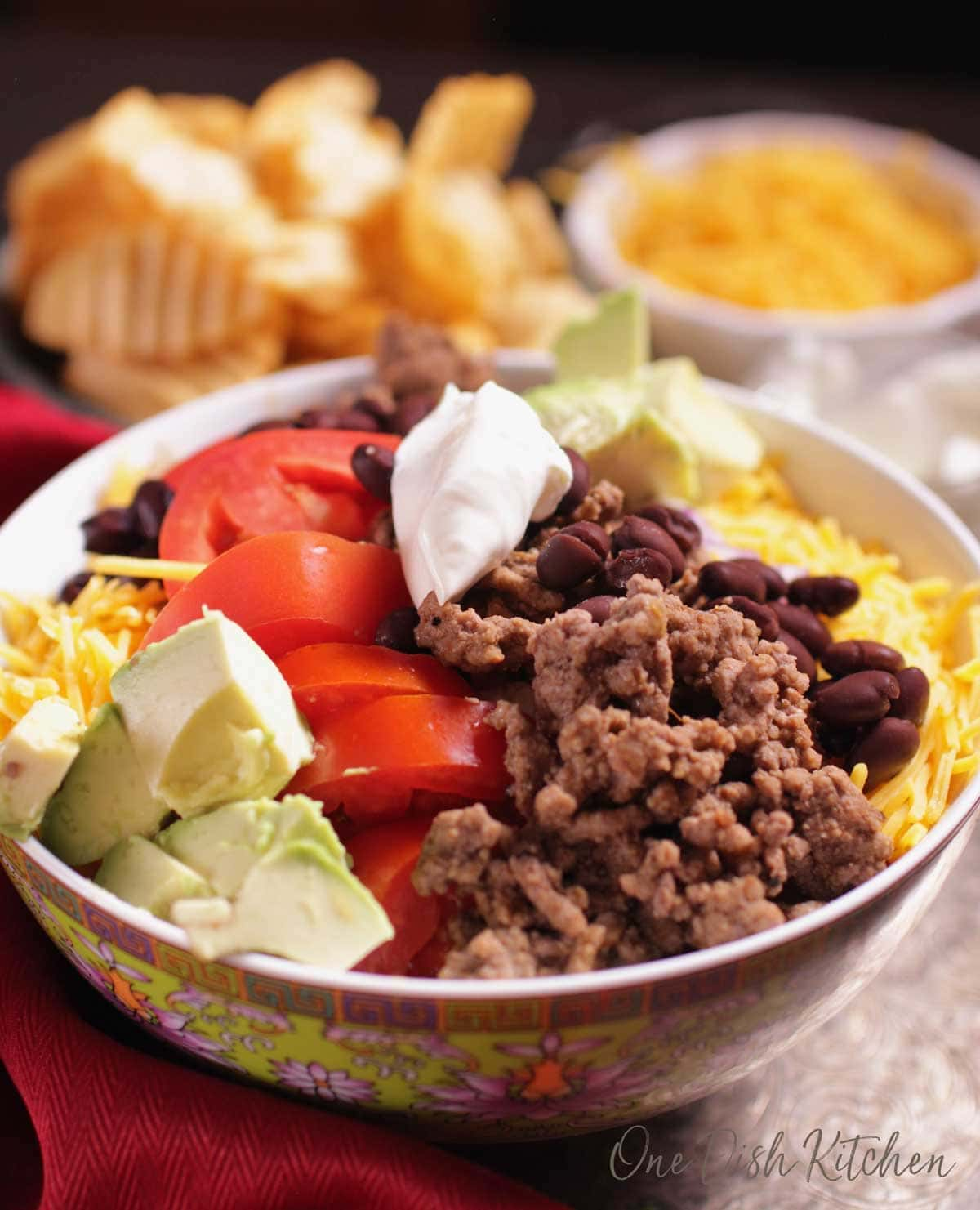 a closeup photo of a taco salad served in a bowl topped with sour cream | one dish kitchen