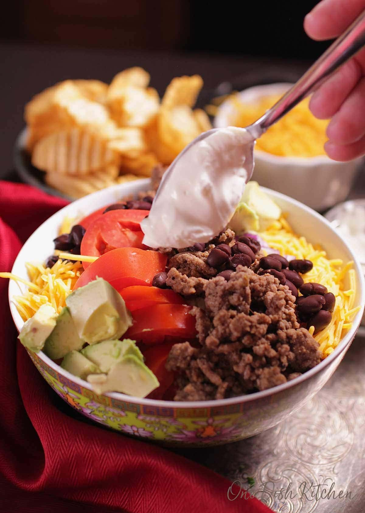 a spoon of sour cream being placed on top of a taco salad in a bowl surrounded by chips and cheese. | one dish kitchen