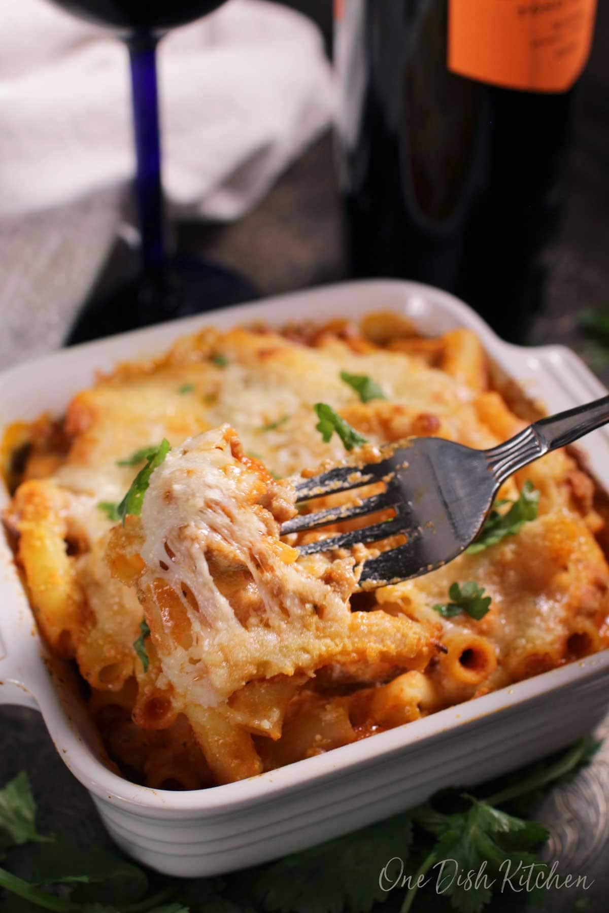 A forkful of a baked ziti casserole with melted cheese hanging from the fork.