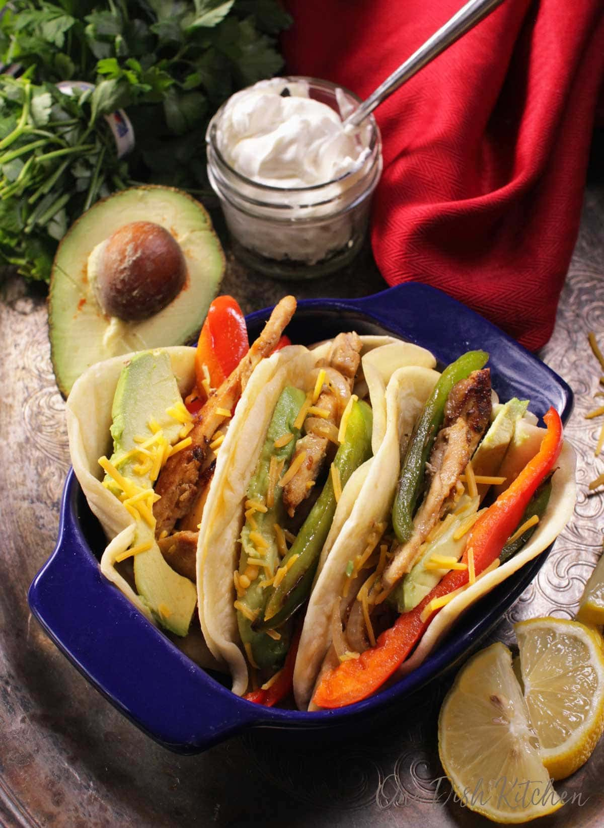 A small baking dish filled with three chicken fajitas filled with avocado slices, red and green bell peppers, and shredded cheese next to a half of an avocado and a small jar of sour cream.