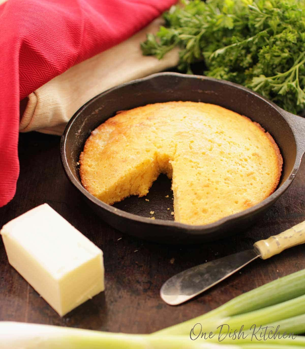 Cornbread in a small cast iron skillet next to a stick of butter and a butter knife