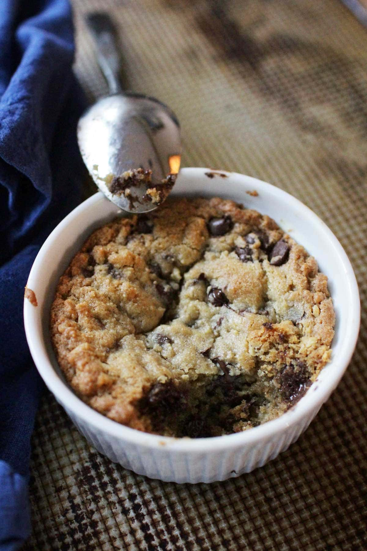 a spoon resting on the edge of a ramekin filled with a deep dish cookie made with chocolate chips | one dish kitchen