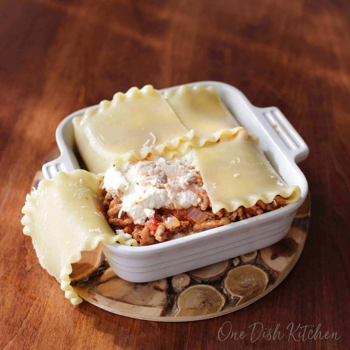 Adding the meat filling to a mini lasagna and folding the noodles over the mixture