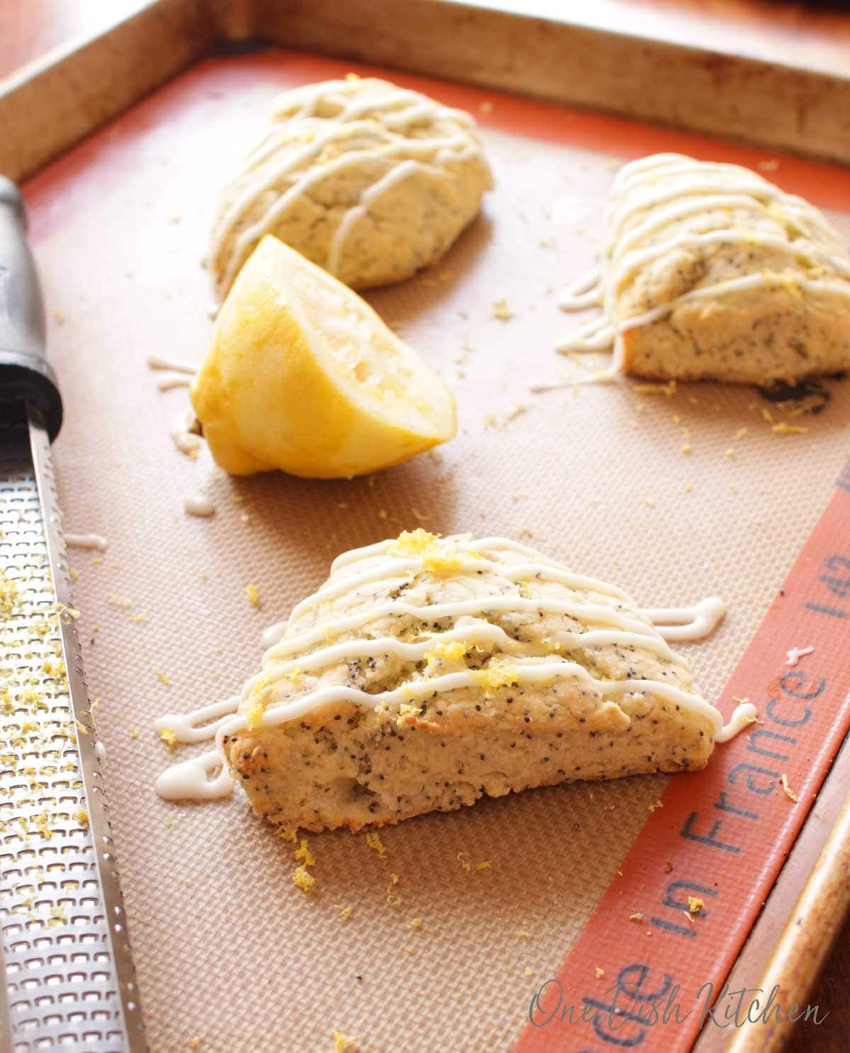 scones on a baking sheet next to a half of a lemon.