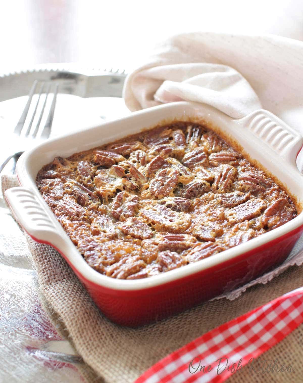a mini pecan pie baked in a small red baking dish | one dish kitchen