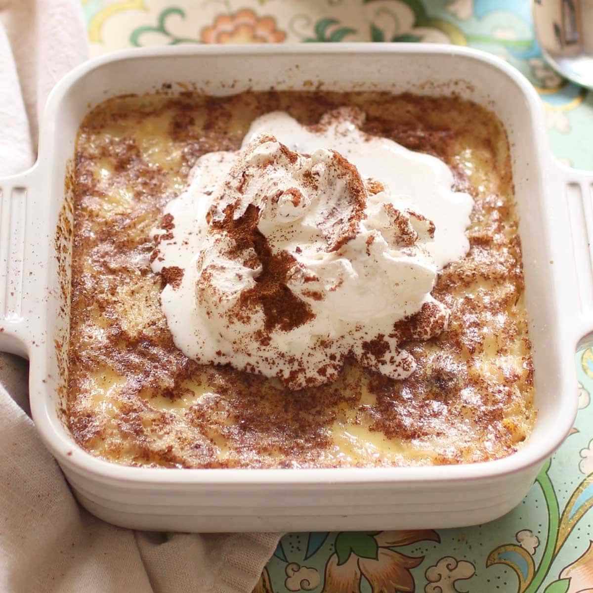 Baked rice pudding topped with whipped cream and ground cinnamon  in small baking dish