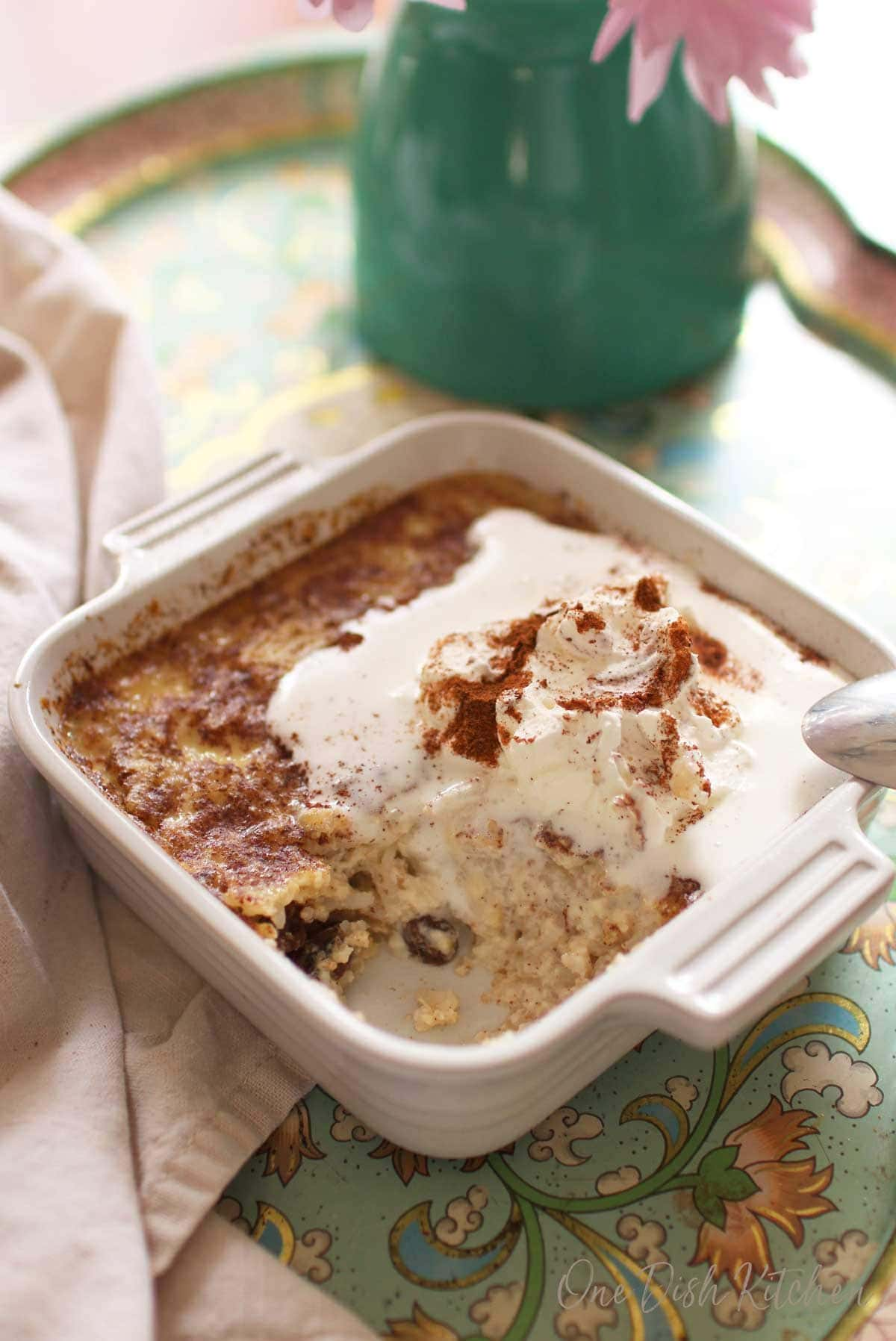 A spoonful missing from the homemade rice pudding topped with whipped cream and ground cinnamon in a small baking dish