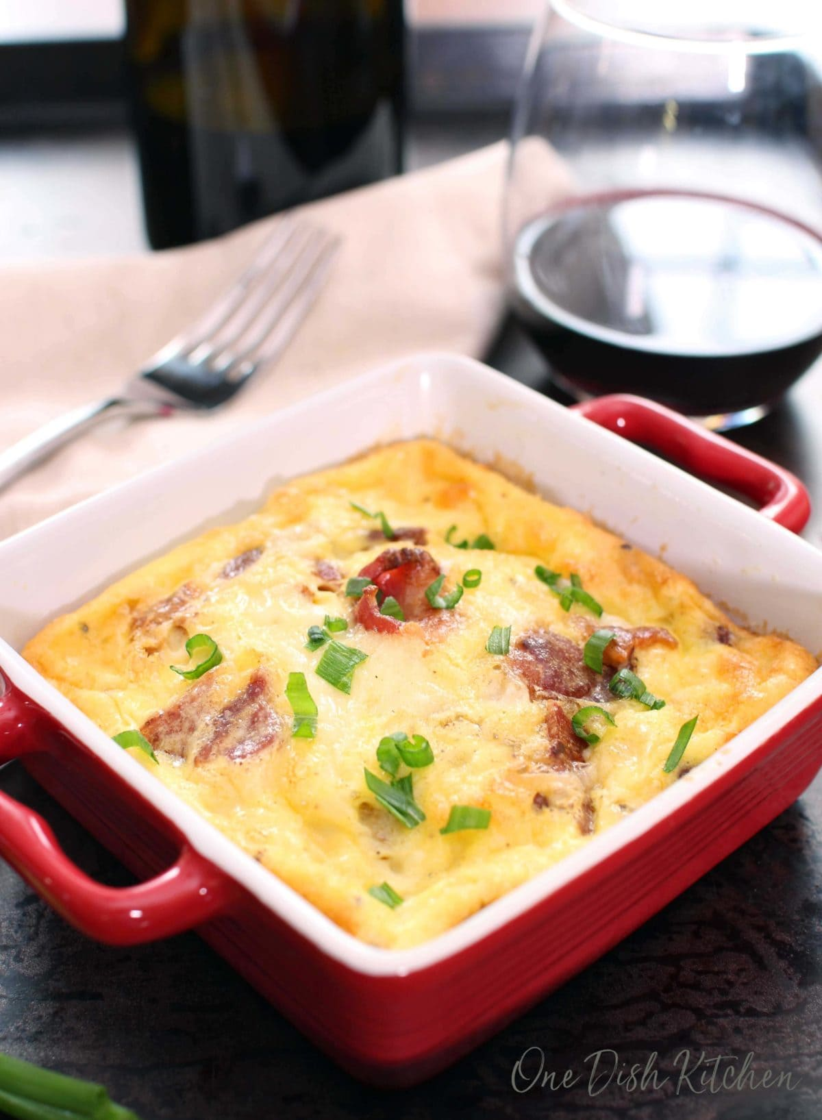 crustless quiche lorraine baked in a small baking dish on a tray with a glass of red wine | one dish kitchen