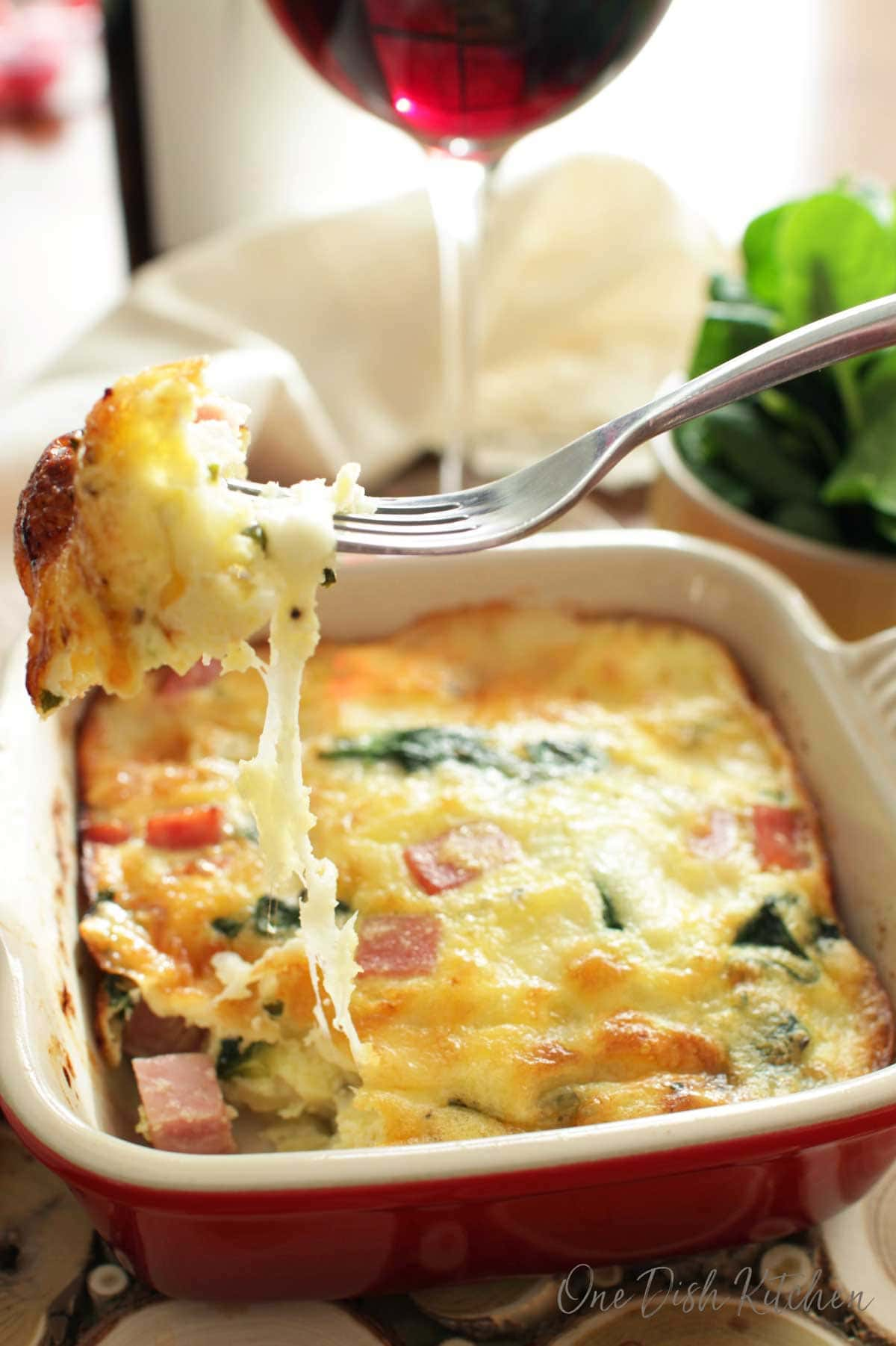 Cheese hanging off a fork in a spinach quiche with a glass of red wine in the background