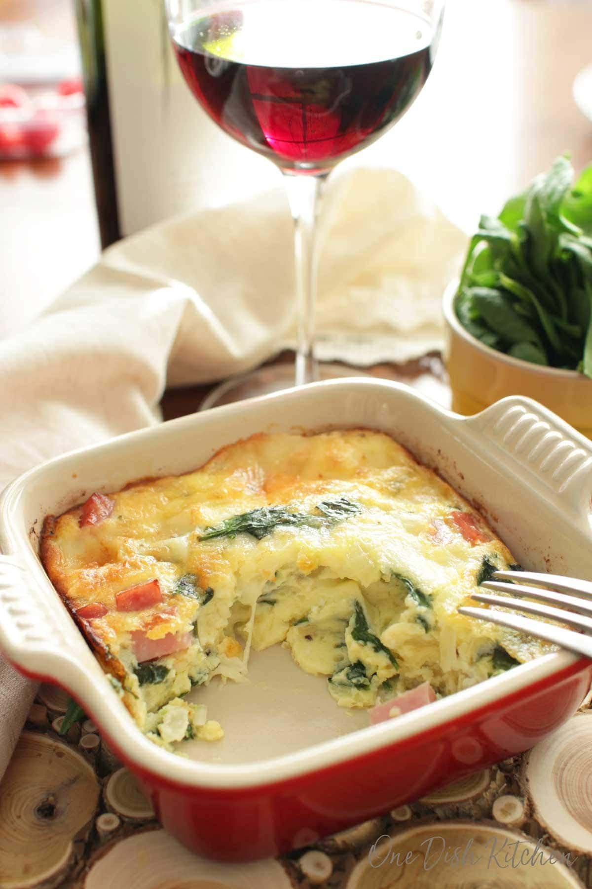 a partially eaten crustless spinach quiche next to a glass of wine | one dish kitchen