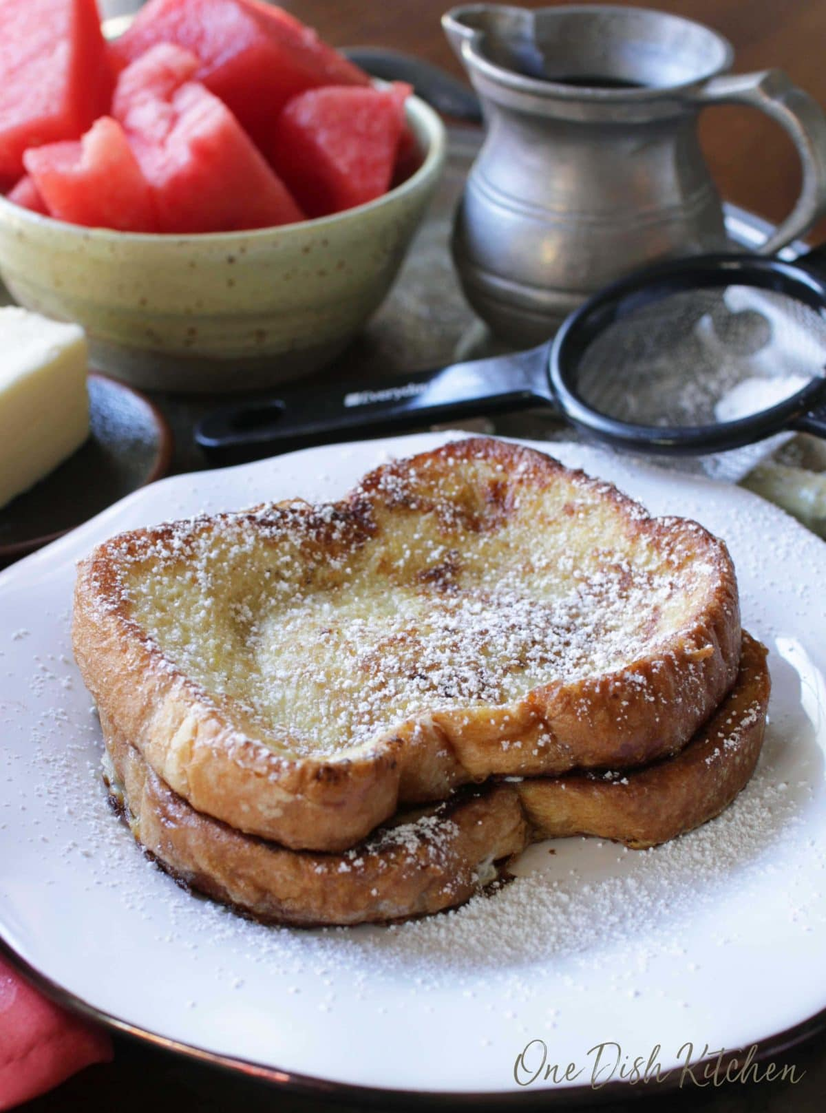 Two french toast slices dusted with powdered sugar on a metal tray with a stick of butter, a bowl of watermelon slices, and a metal container of maple syrup
