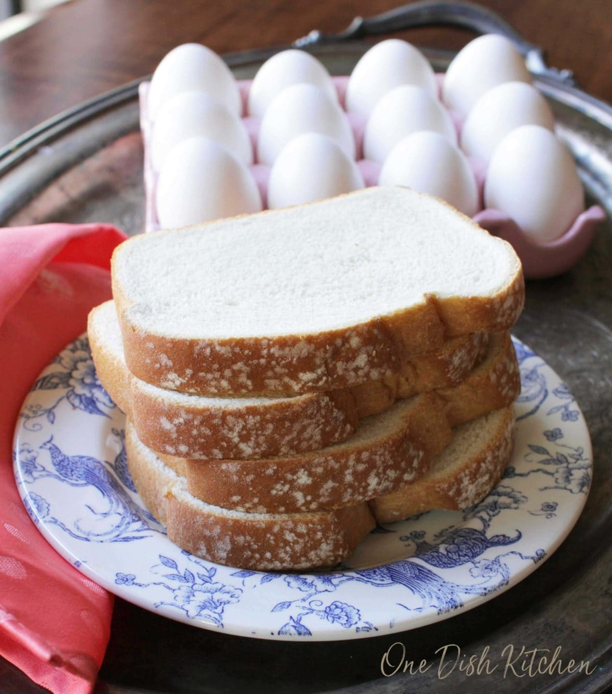 Four slices of white bread on a plate next to a tray of a dozen eggs and a red cloth napkin all on a metal tray