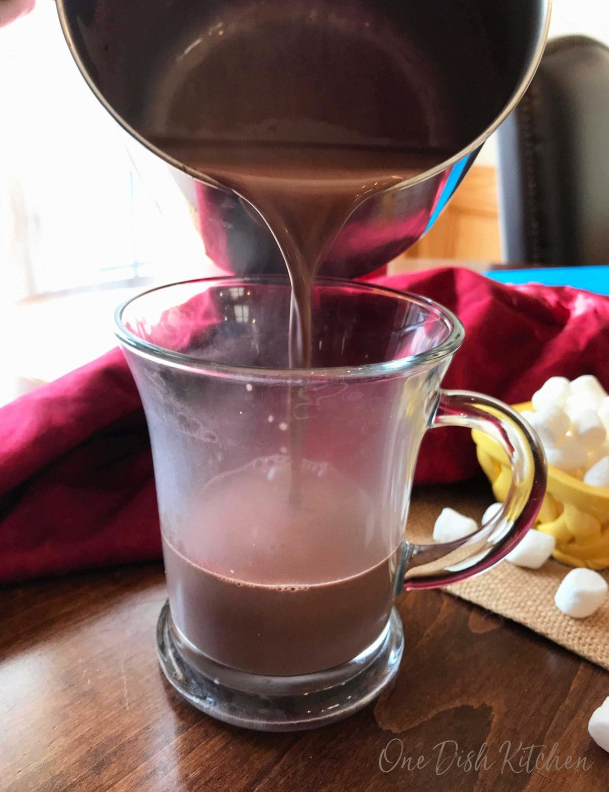 Pouring hot chocolate from a pot and into a mug with a small bowl of mini marshmallows in the background
