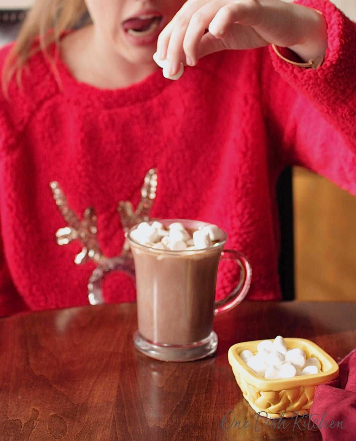 A young girl adding mini marshmallows to a cup of hot chocolate