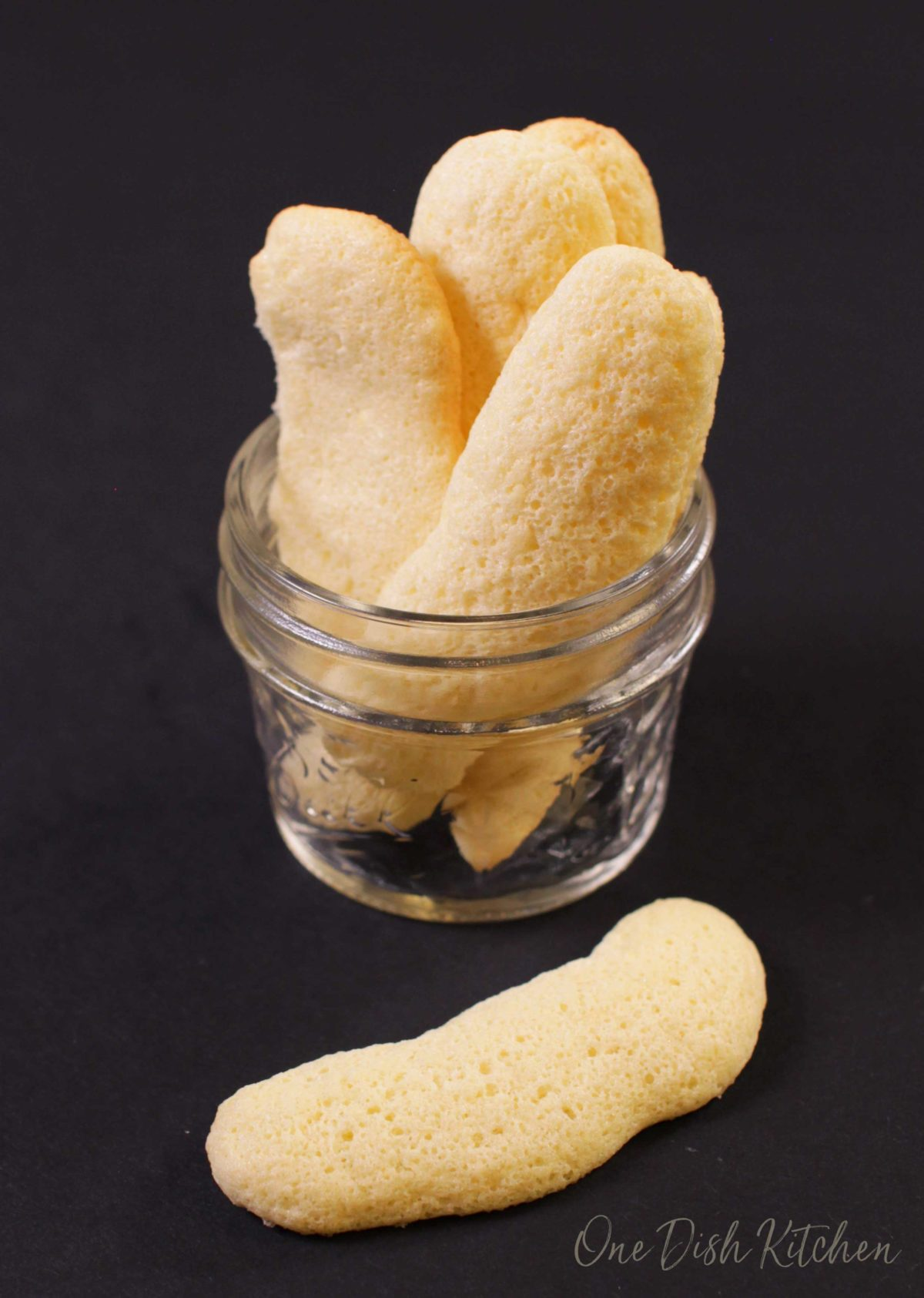 A small jar filled with four homemade ladyfingers with one lady finger laying next to the jar