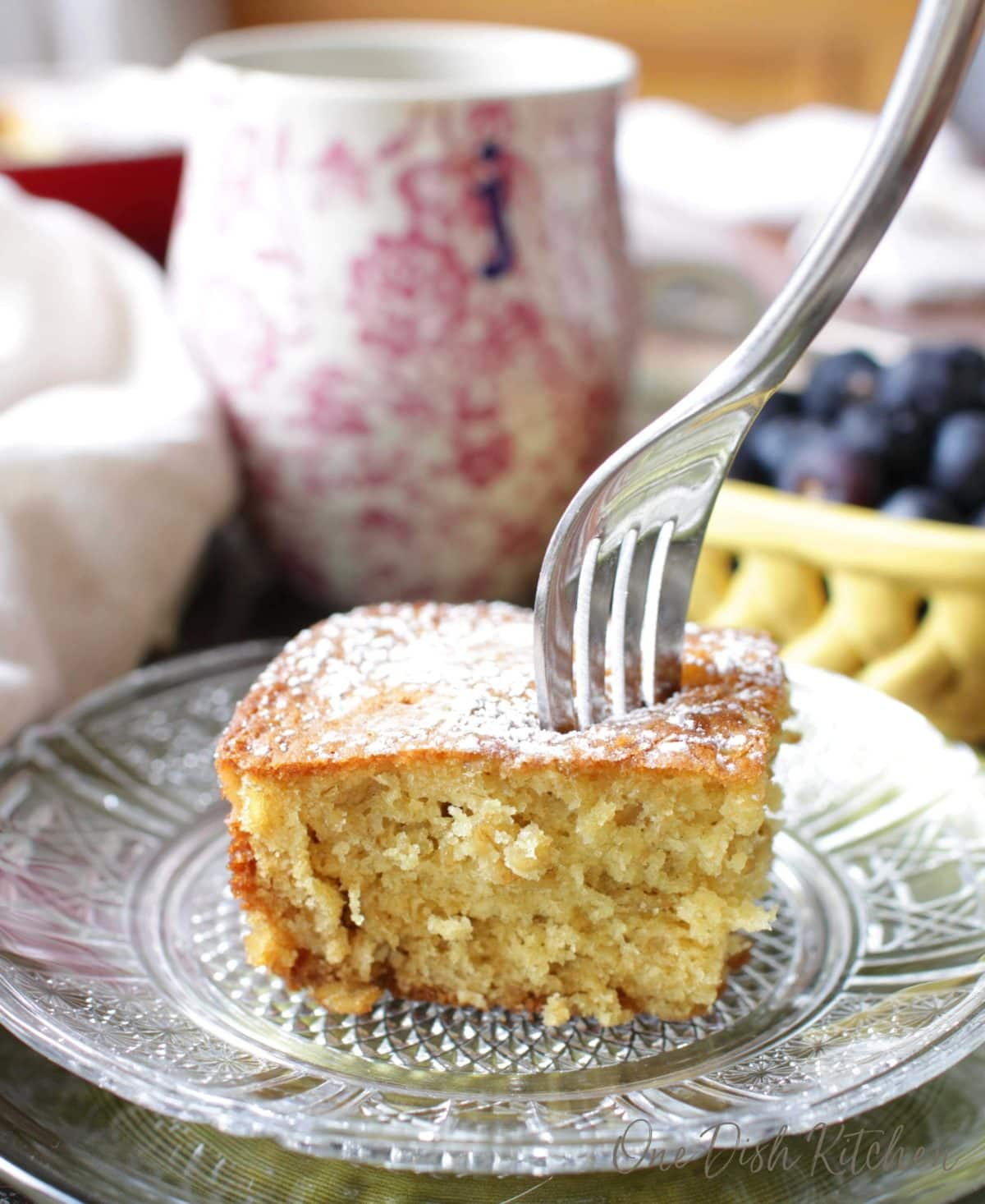 A fork piercing the top of a slice of orange oatmeal cake topped with powdered sugar next to a coffee mug and a small bowl of blueberries