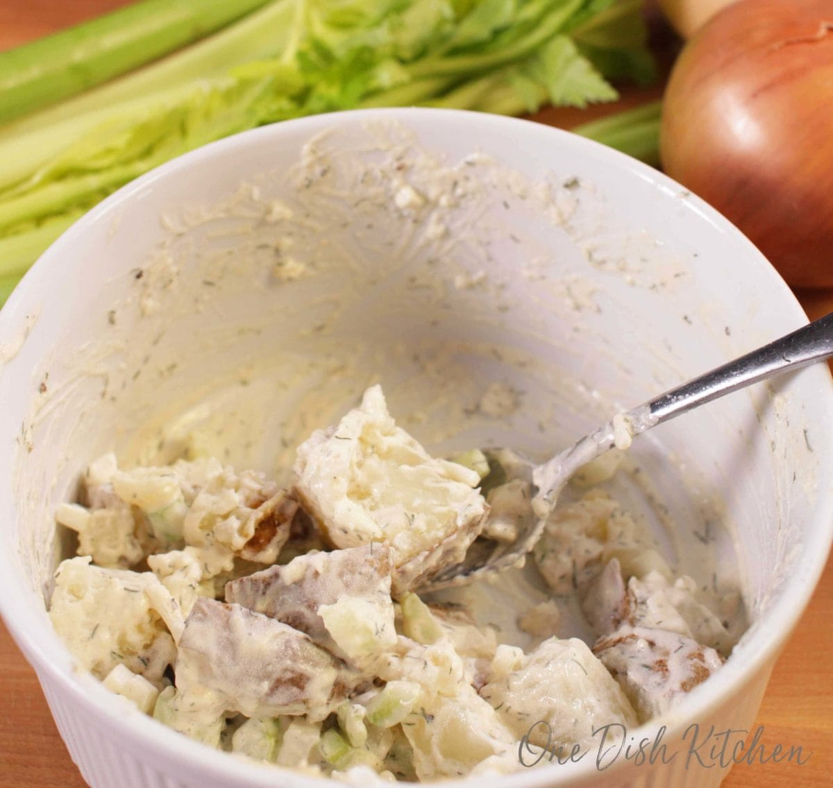 mixing onions, celery, potatoes, mayonnaise, and mustard together in a bowl to make potato salad.