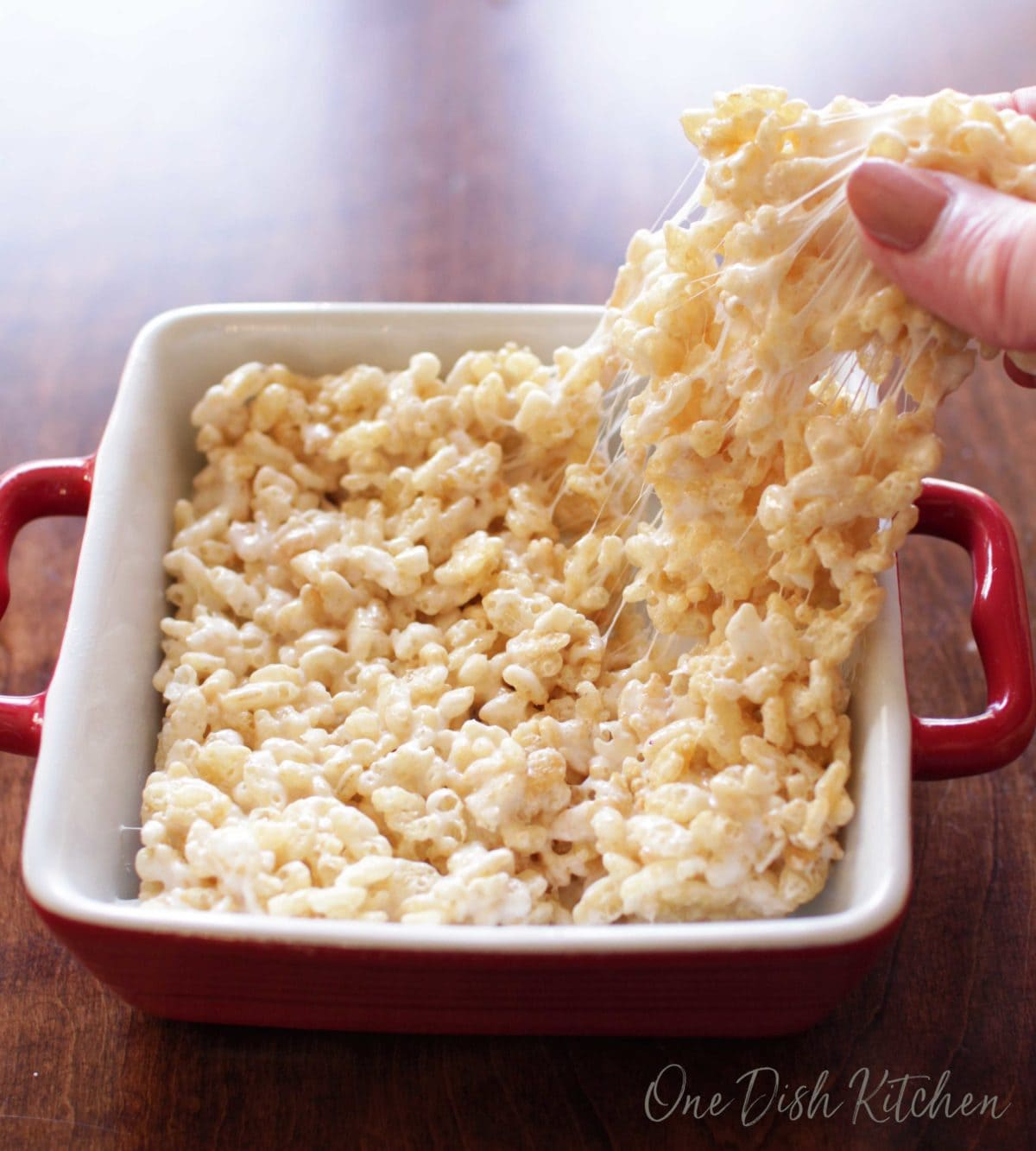 Pulling off a piece of a rice krispie treat with fingers from a small baking dish