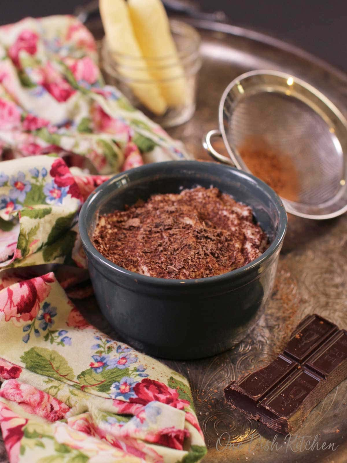 A mini tiramisu topped with chocolate shavings in a circular dish on a metal tray with a floral cloth napkin, a piece of a chocolate bar, and cocoa powder in a sieve