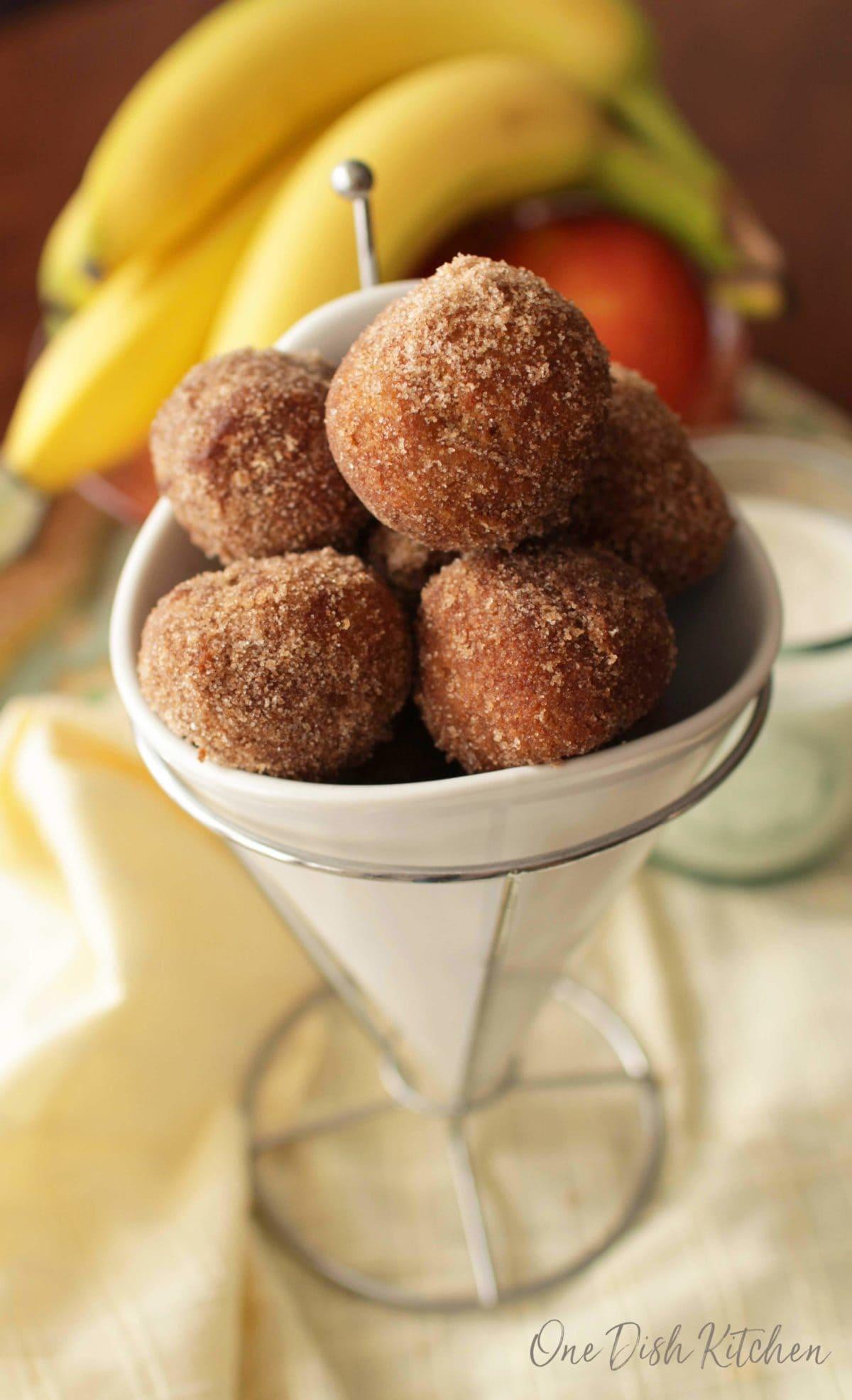 A closeup of a bowl of cinnamon sugar donut holes