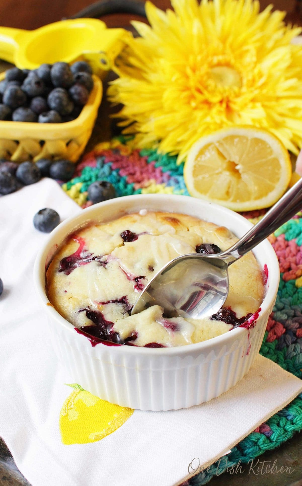 A spoonful of lemon blueberry muffin in a ramekin topped with sugar glaze on a metal tray surrounded by blueberries, half of a lemon, and a big yellow flower.