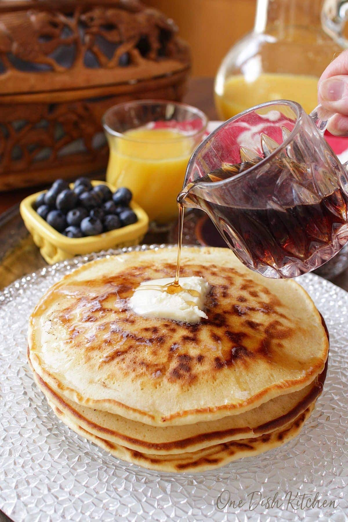 Pouring syrup over stack of pancakes on a plate topped with melting butter next to a small bowl of blueberries and a glass of orange juice
