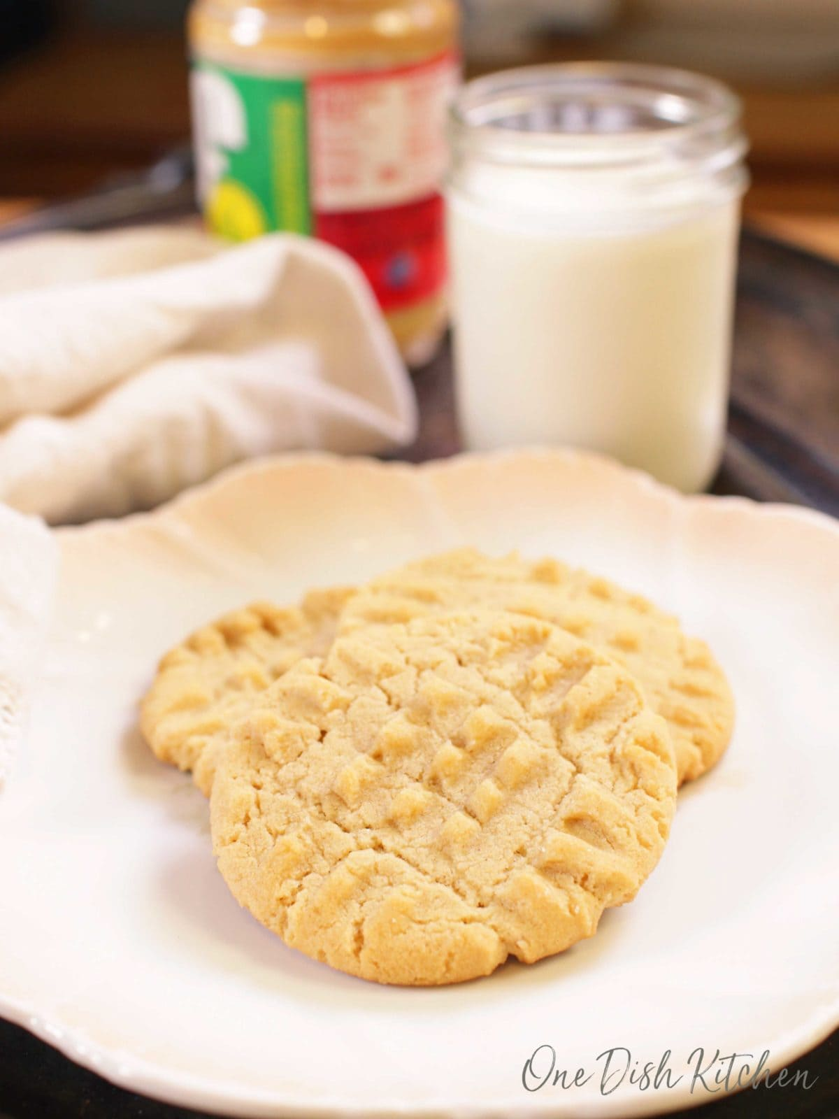 peanut butter cookies on a plate next to a jar of peanut butter and a glass of milk.