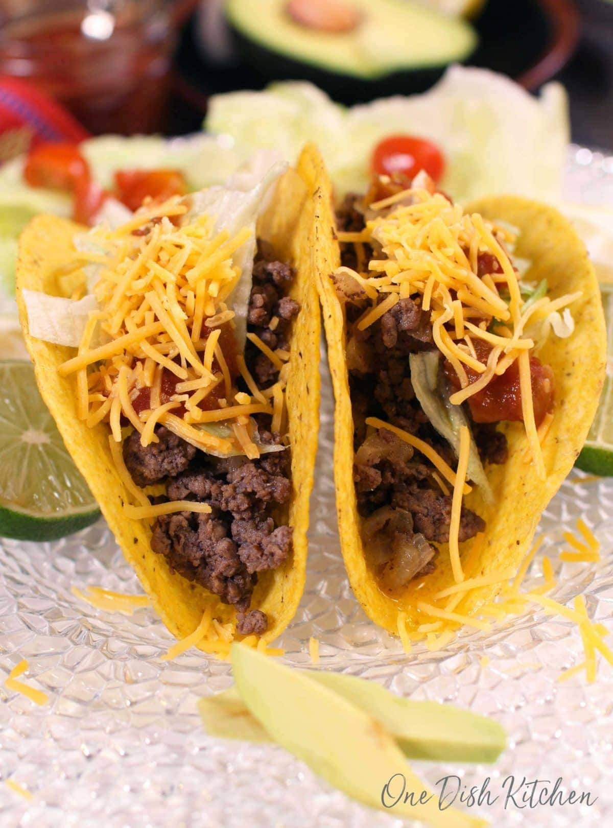 Two beef tacos topped with salsa, lettuce, and shredded cheese on a plate next to sliced lime wheels and tomatoes.