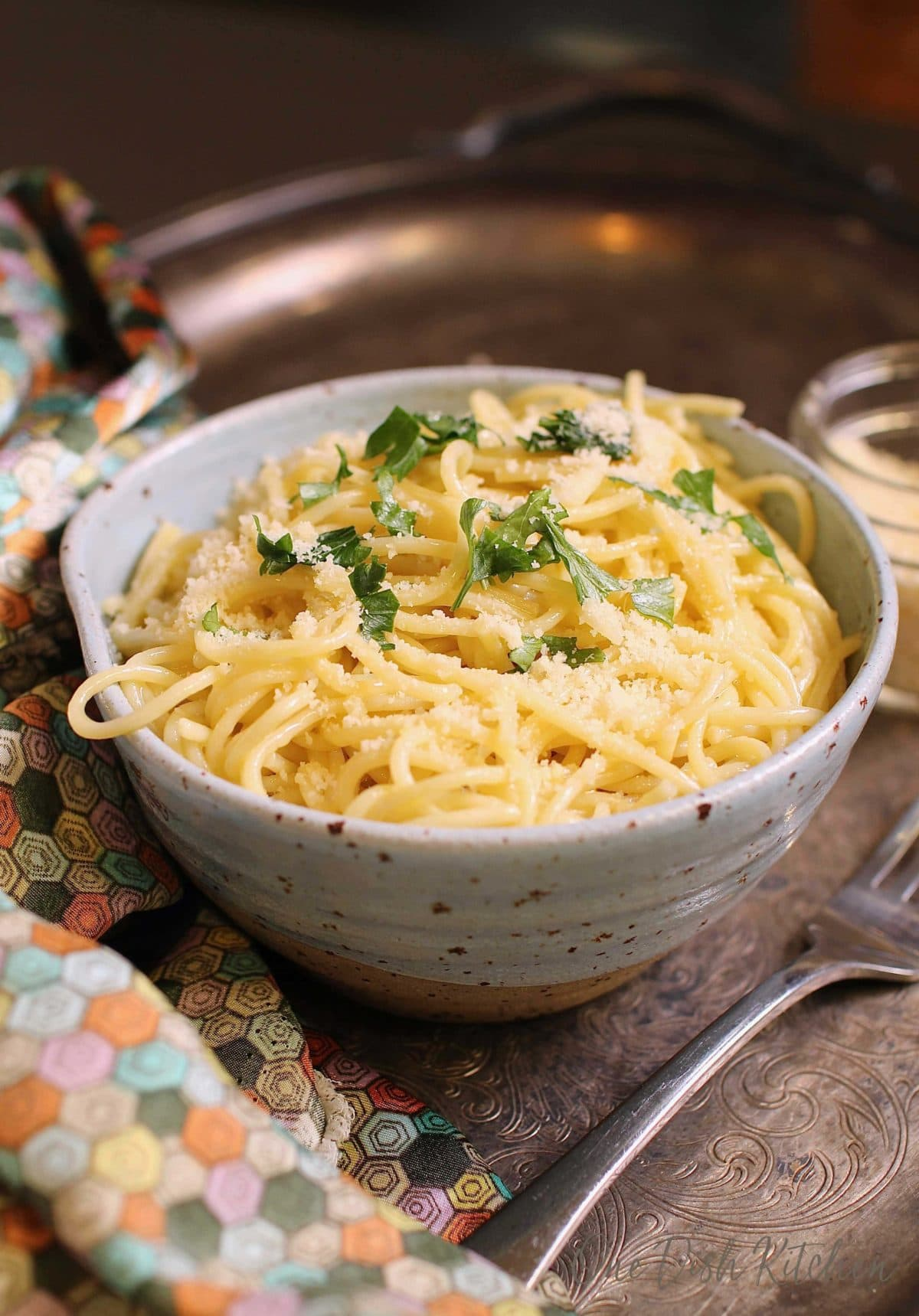 Spaghetti noodles topped with parmesan cheese and chopped parsley in a bowl next to a fork on a metal tray