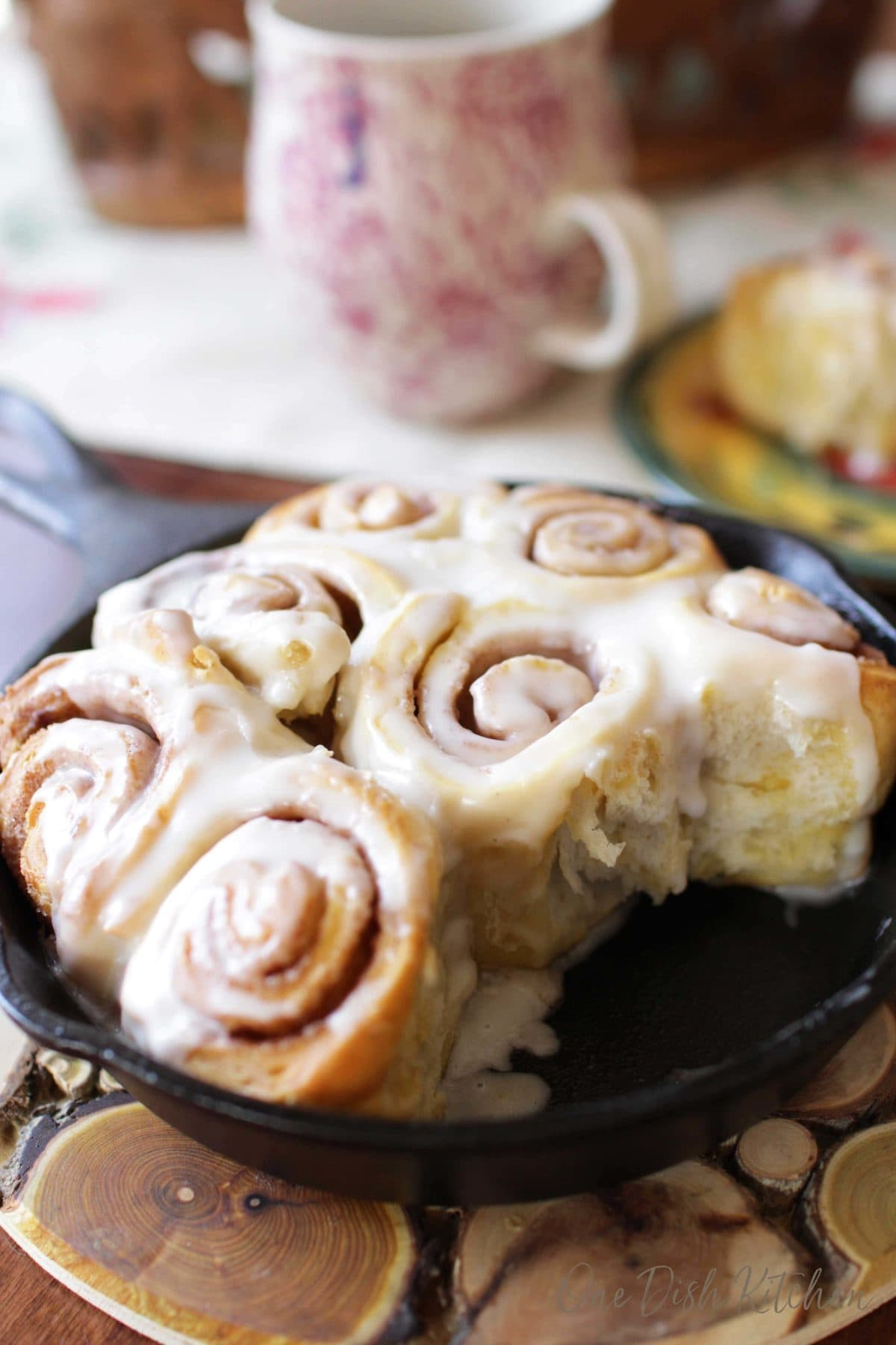 A closeup of cinnamon rolls on a small skillet with a few missing on a wooden trivet next to a cup of coffee.