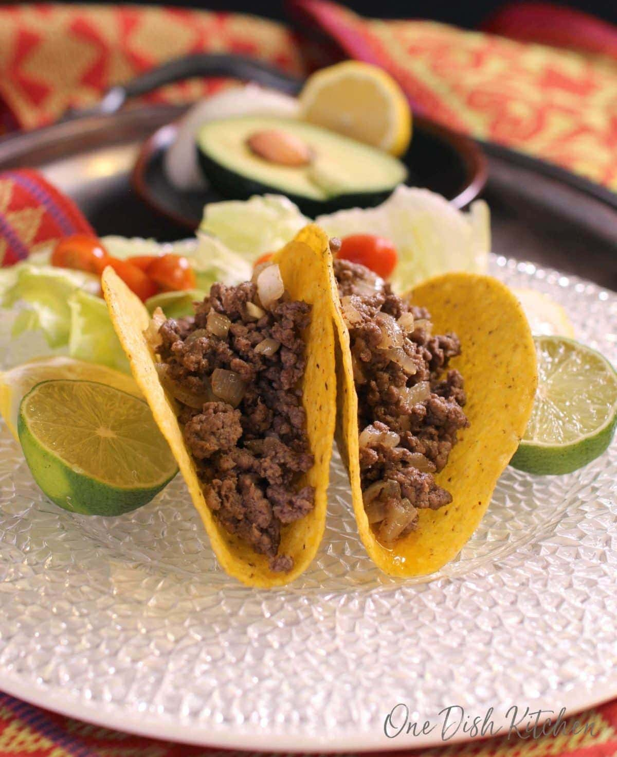 Two taco shells on a plate filled with ground beef and onions with lime halves on both sides of the tacos and a small salad on a metal tray with small plate of half of an avocado and half of a lemon in the background