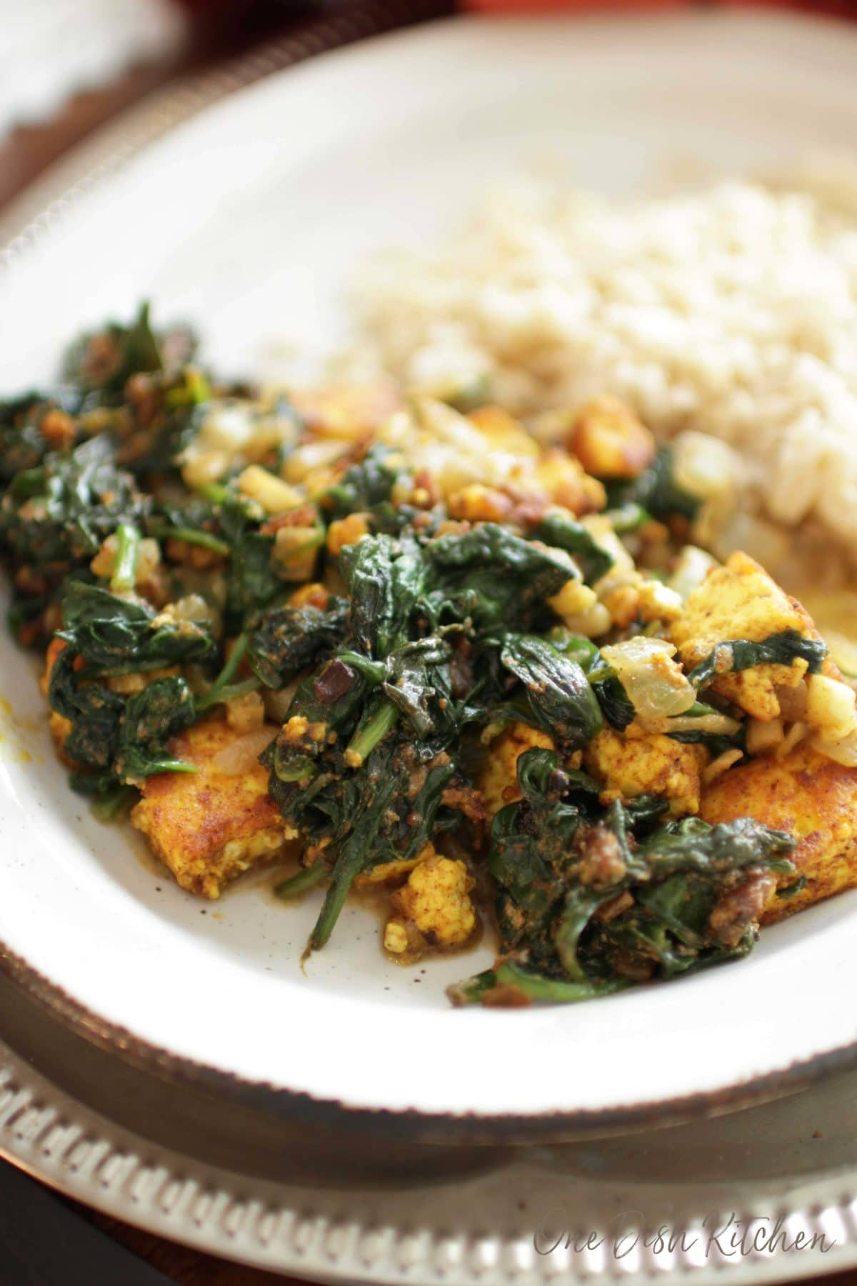 A close up of saag paneer on a plate with white rice