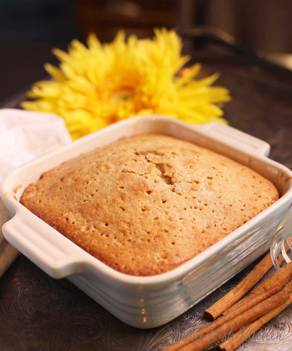 A spice cake in a small square baking dish next to yellow flowers and cinnamon sticks all on a metal tray