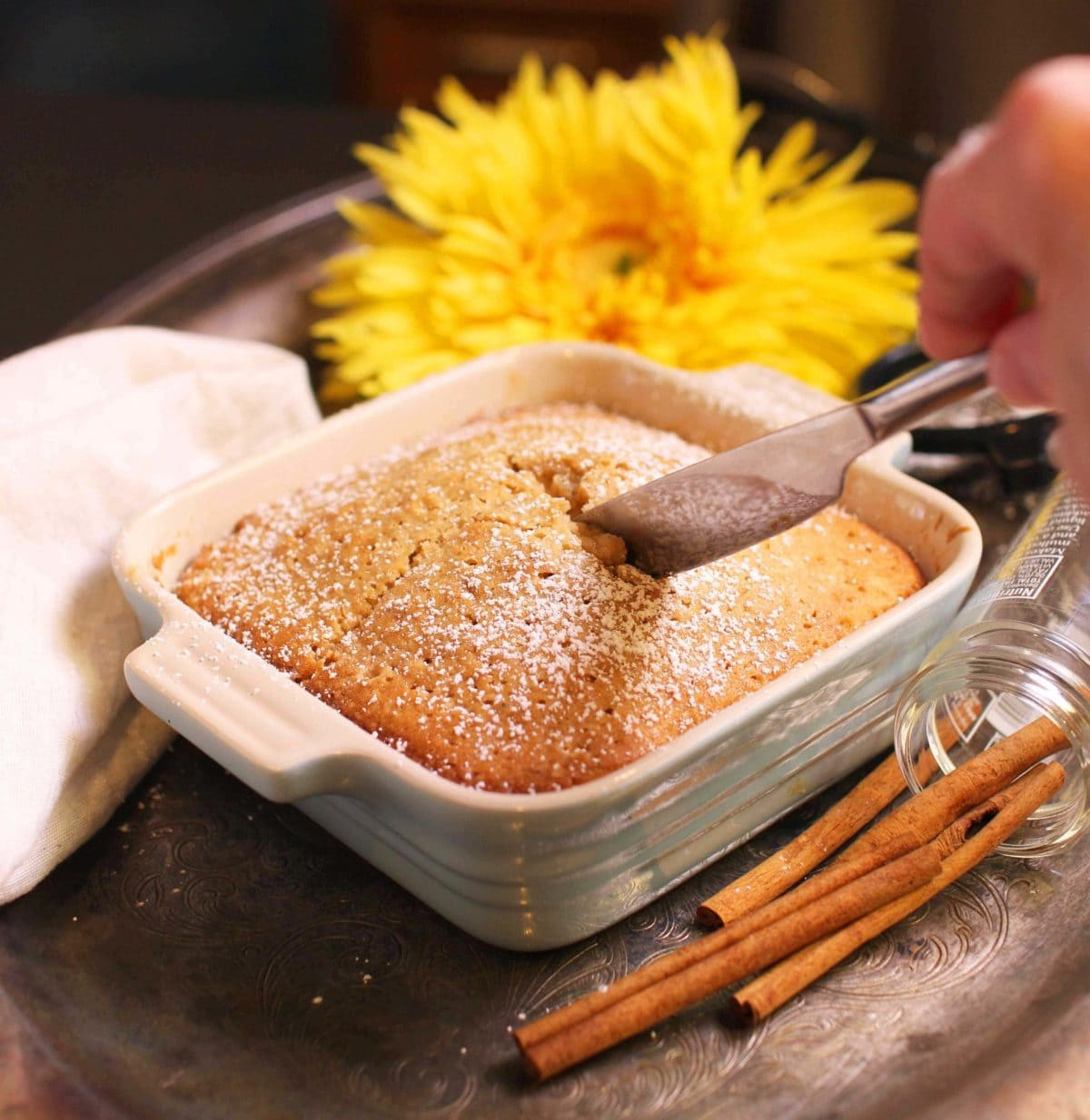 A knife cutting a piece of spice cake dusted with powdered sugar from a small baking dish on a metal tray with yellow flowers and cinnamon sticks