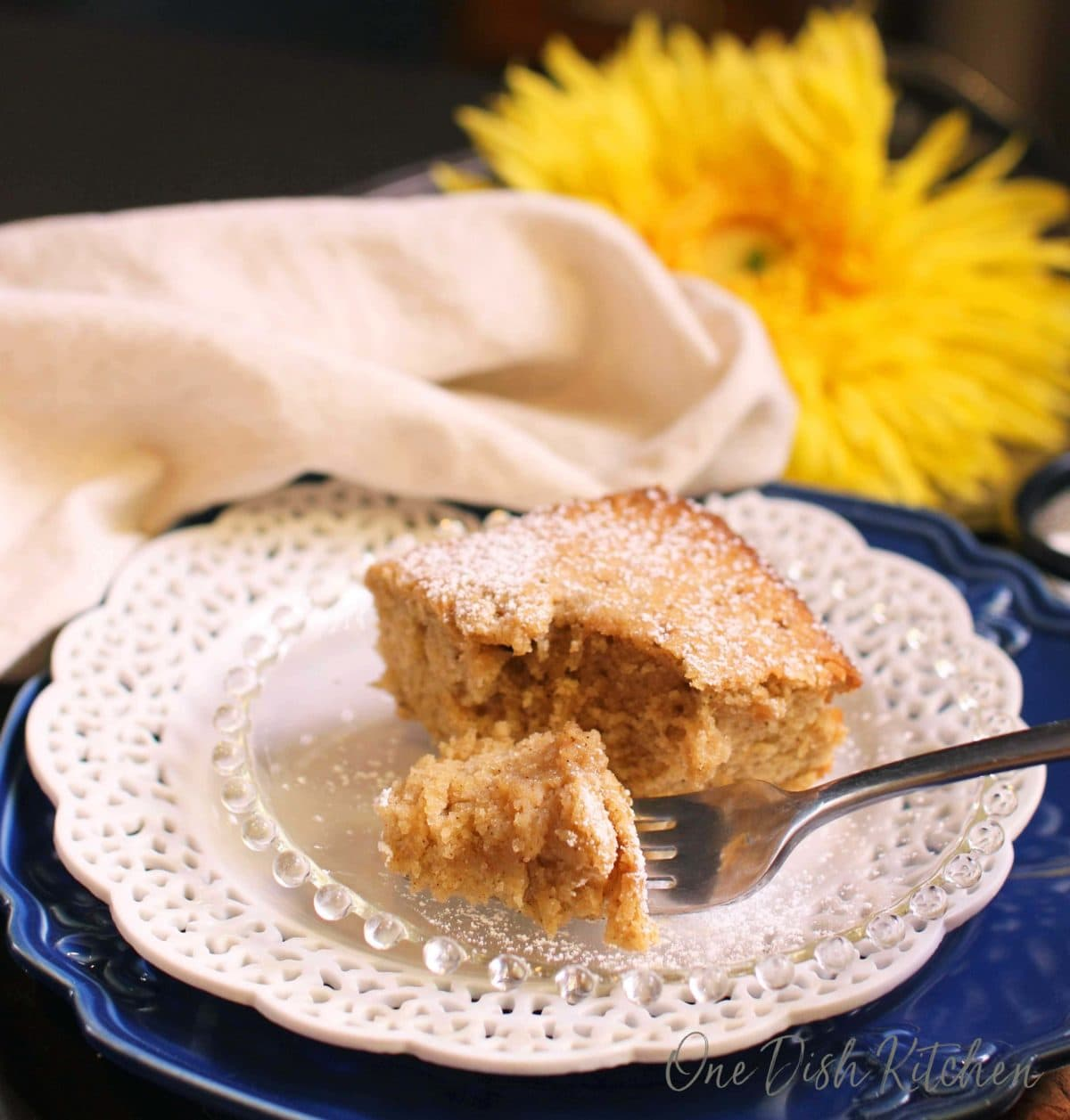 A square piece of spice cake dusted with powdered sugar on a small plate with a fork