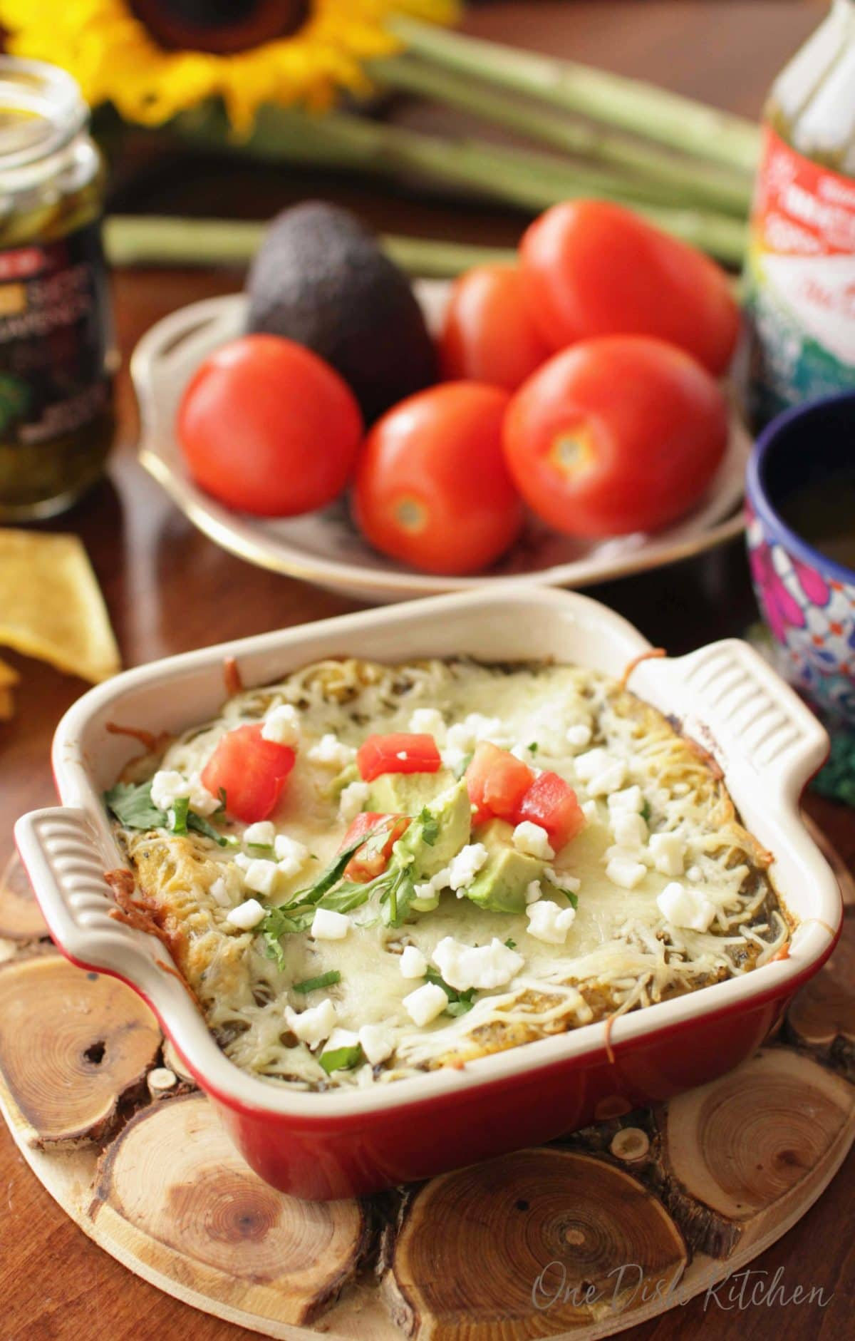 Enchiladas topped with crumbled cotija cheese and chopped avocado and tomatoes in a small baking dish on a wooden trivet next to a bowl of tomatoes an avocados