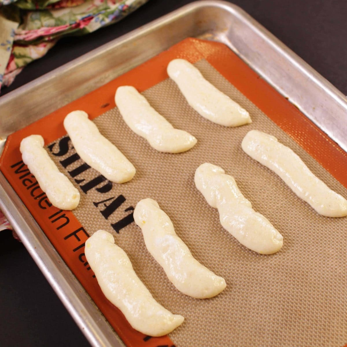 ladyfinger batter piped onto a small cookie sheet.