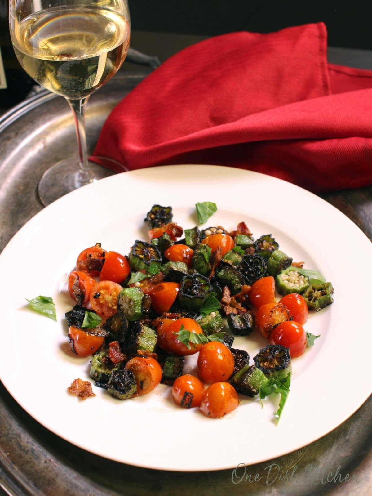 Fried okra, bacon, and tomatoes plated on a metal tray with a glass of white wine and a red cloth napkin