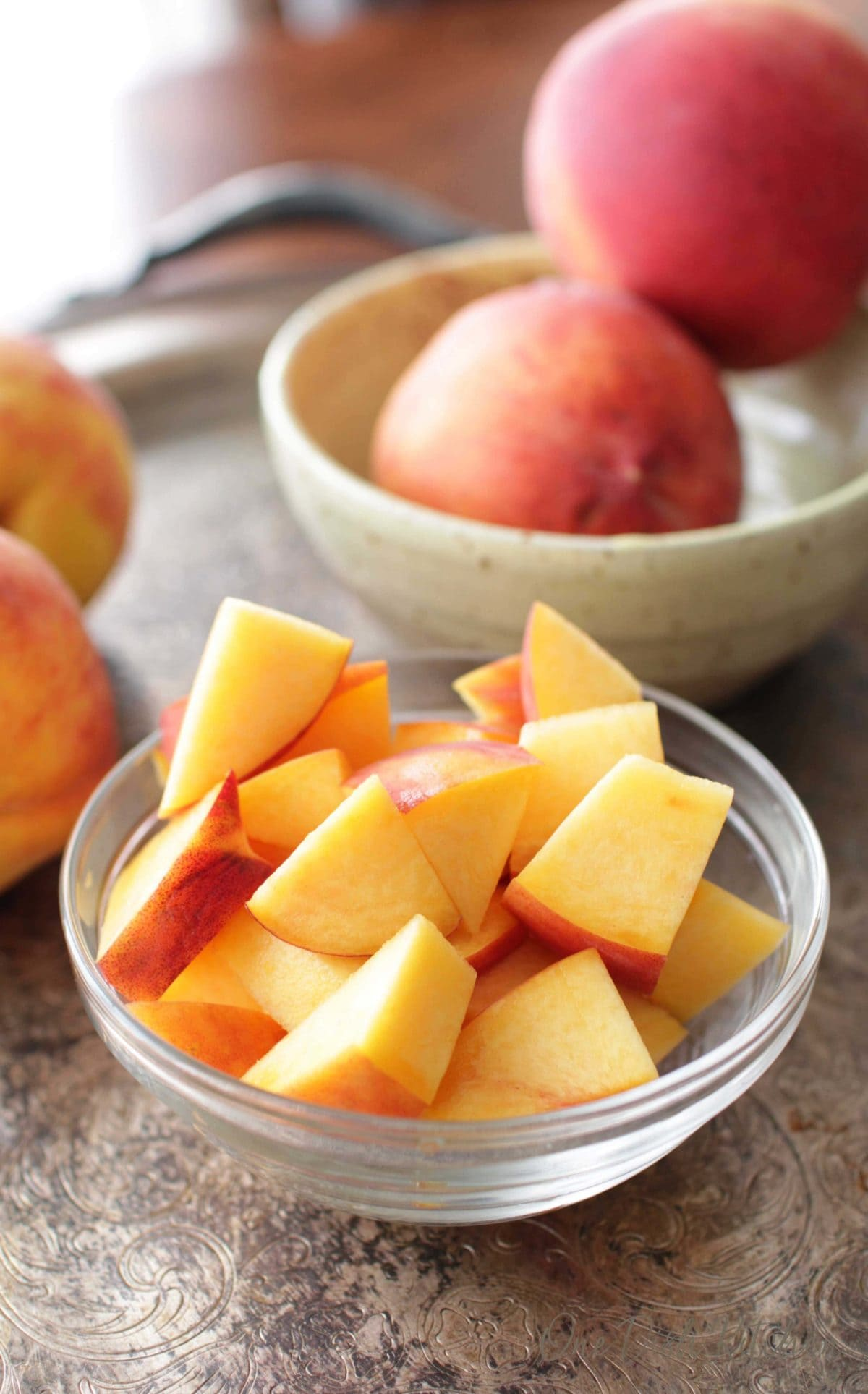 A small bowl filled with chopped peaches next to a bowl of whole peaches on a metal tray.